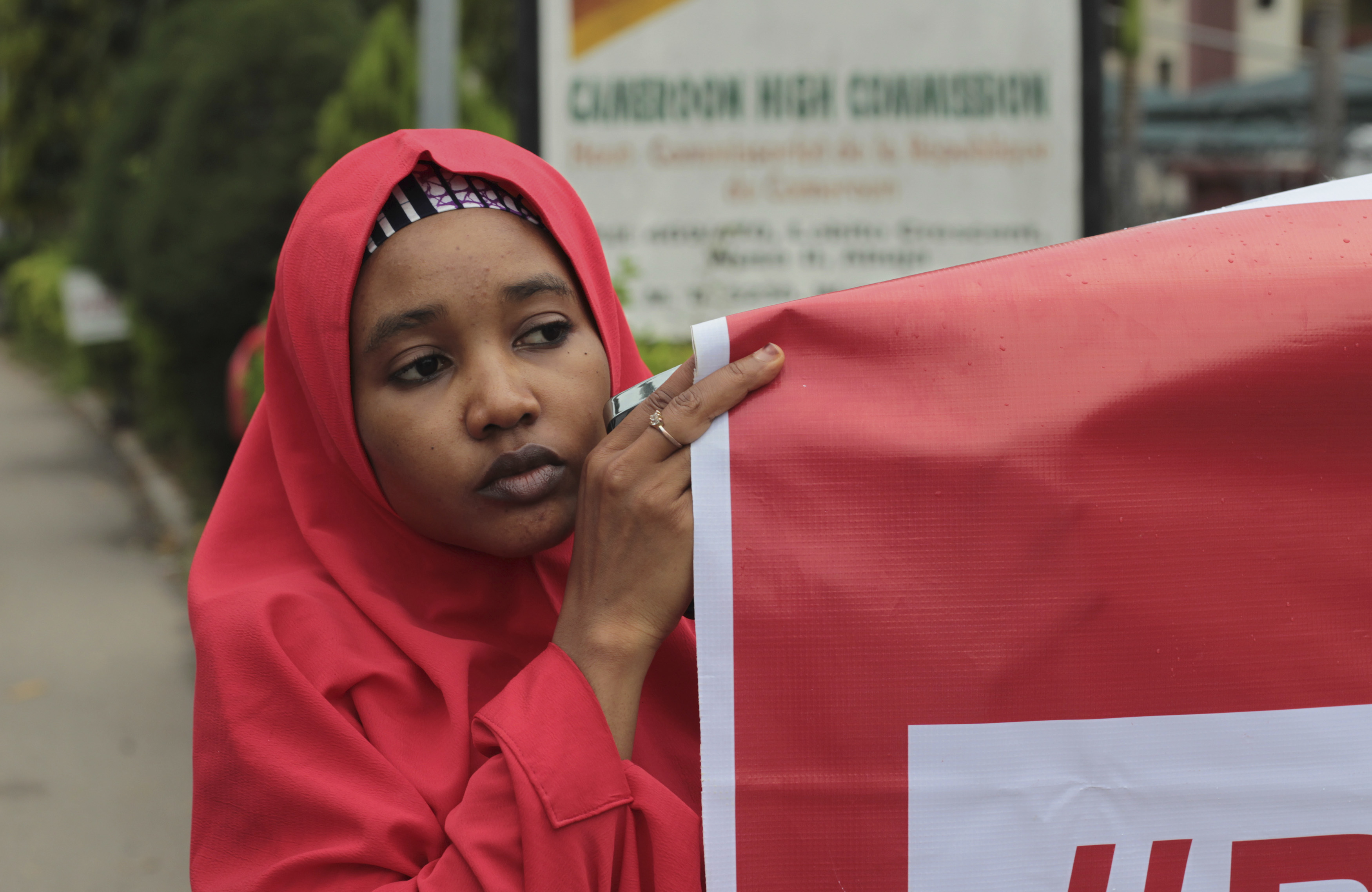 "FILE - A campaigner from ""#Bring Back Our Girls"" hold a banner during a rally calling for the release of the Chibok school girls who were abducted by the Boko Haram militants, outside the Cameroon Embassy in Abuja."