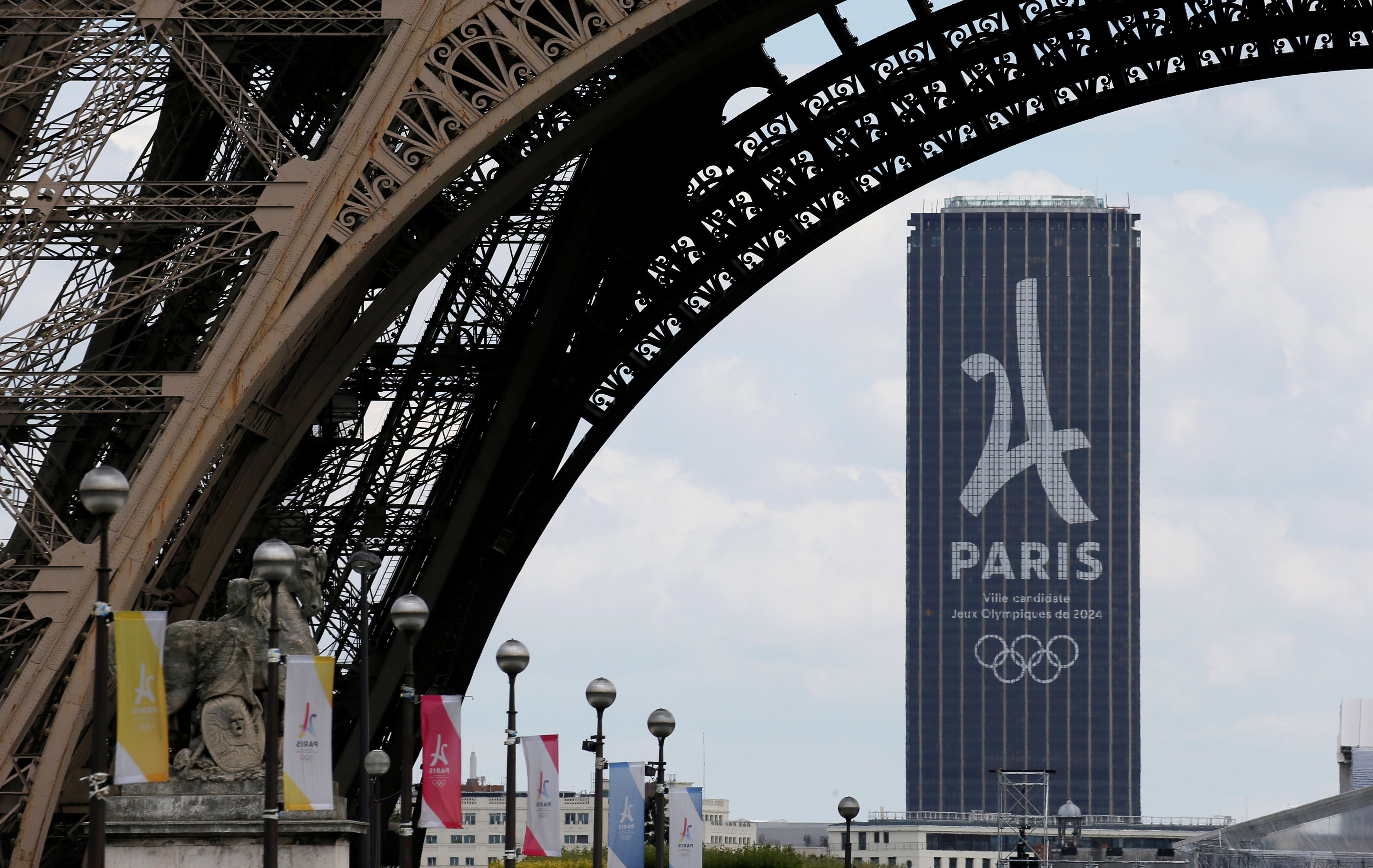 FILE - The logo of the Paris candidacy for the 2024 Olympic and Paralympic Games is seen on the Montparnasse tower behind the Eiffel Tower in Paris, July 11, 2017.