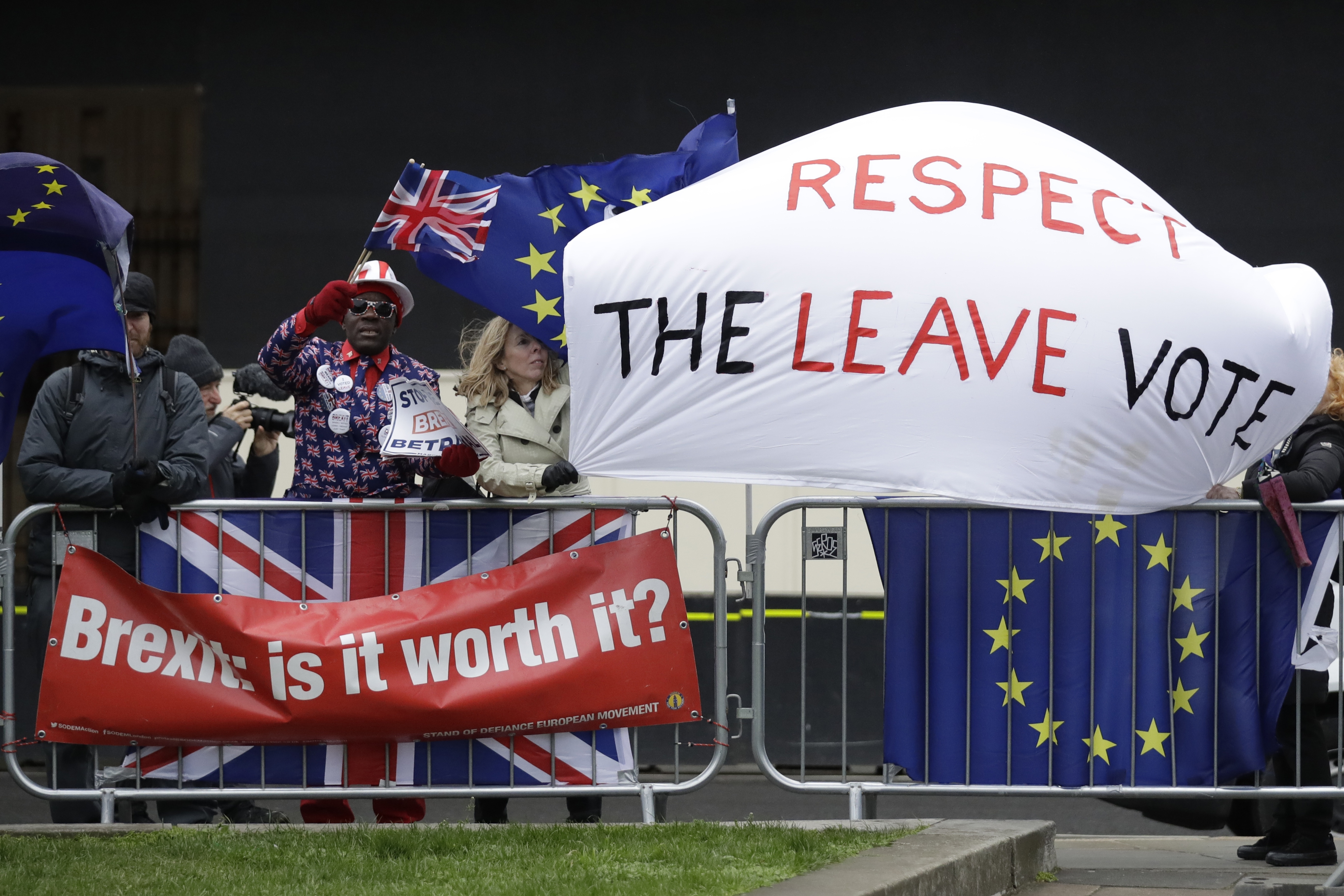 Signs of Brexit supporters and opponents are seen outside the Houses of Parliament in London, Britain, March 12, 2019.