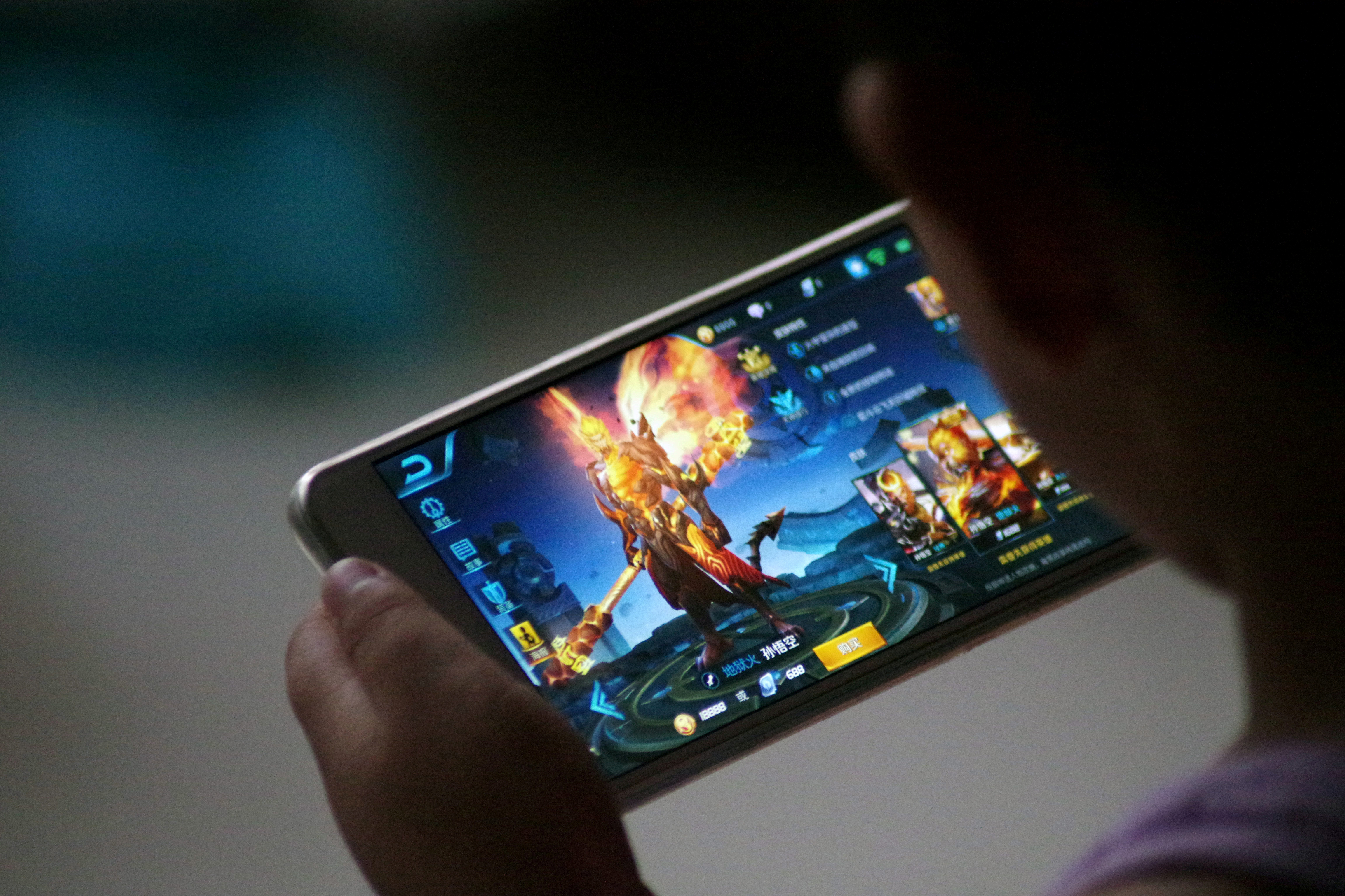 FILE - A child plays the game Honour of Kings by Tencent at home in Dezhou, Shandong province, China, July 2, 2017.
