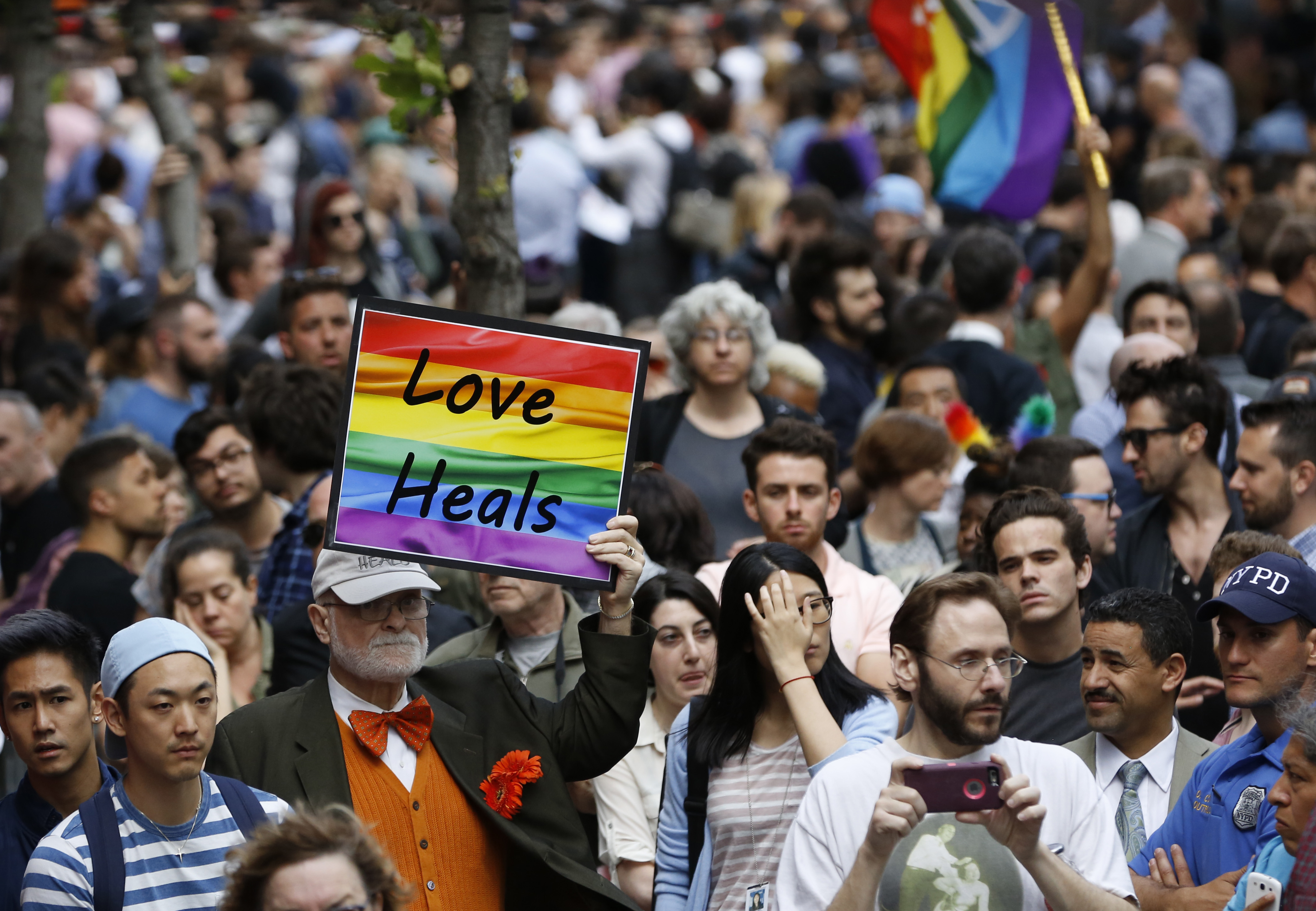 A man walks through the crowd holding a sign during a vigil and memorial for victims of the Orlando nightclub shootings near the historic Stonewall Inn in New York, June 13, 2016.