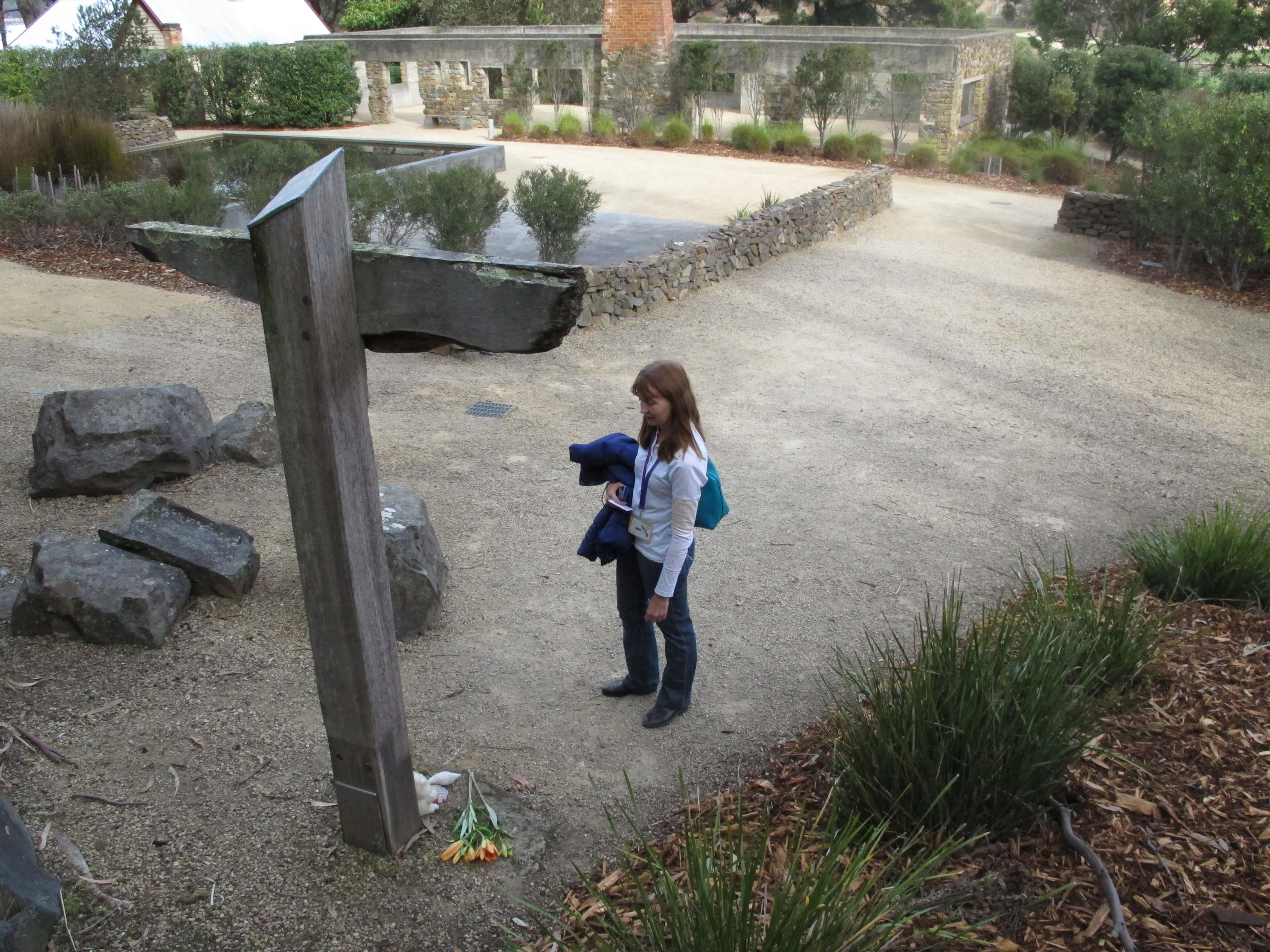 FILE - A tourist reads names on a memorial, at Port Arthur, Tasmania state, Australia, where 35 people were killed by a lone gunman, April 18, 2016. The 1996 massacre galvanized Australia to drastically clamp down on guns.