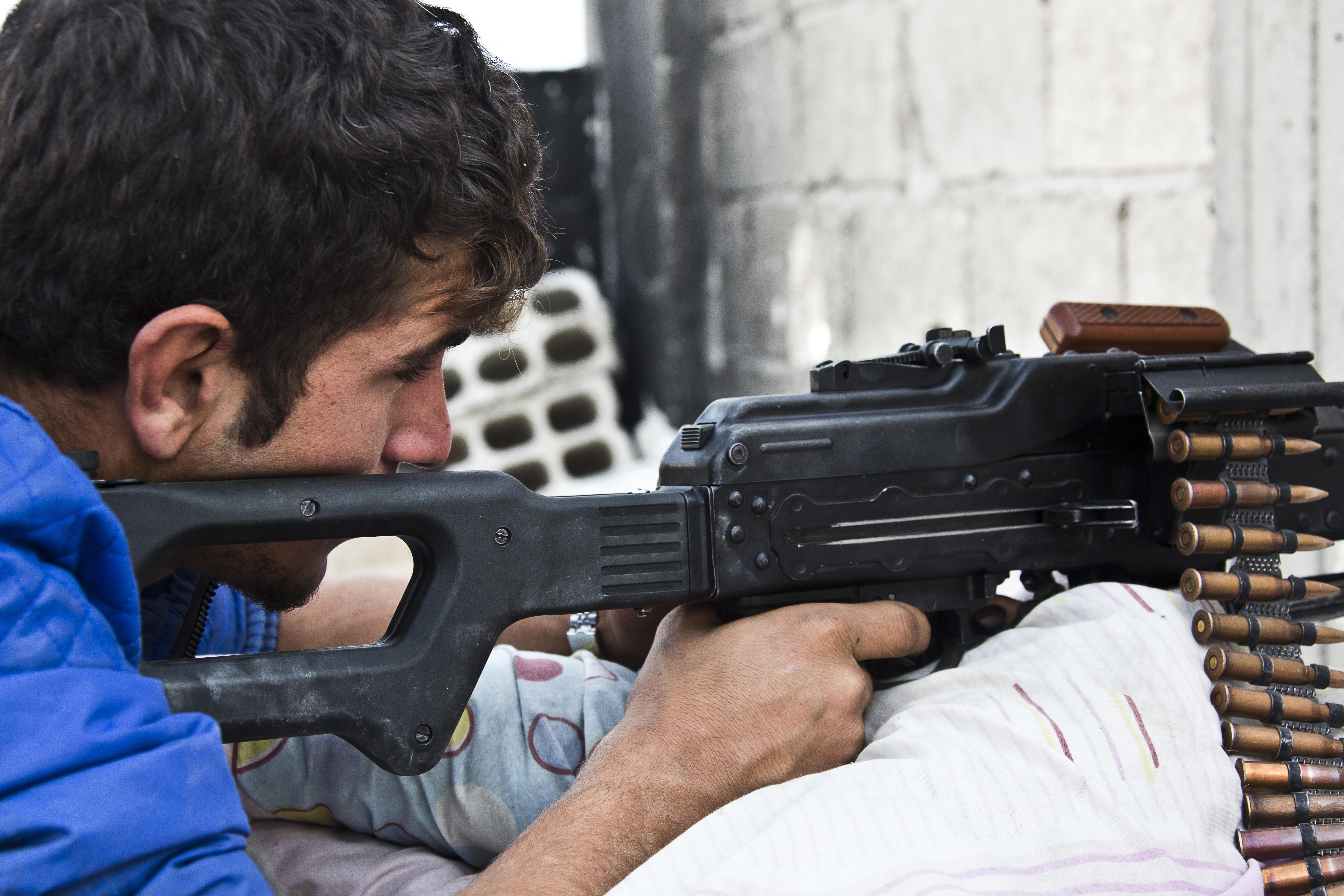FILE - Young Kurdish People's Protection Units (YPG) fighter who recently volunteered holds a position with his weapon in Kobani, Syria.