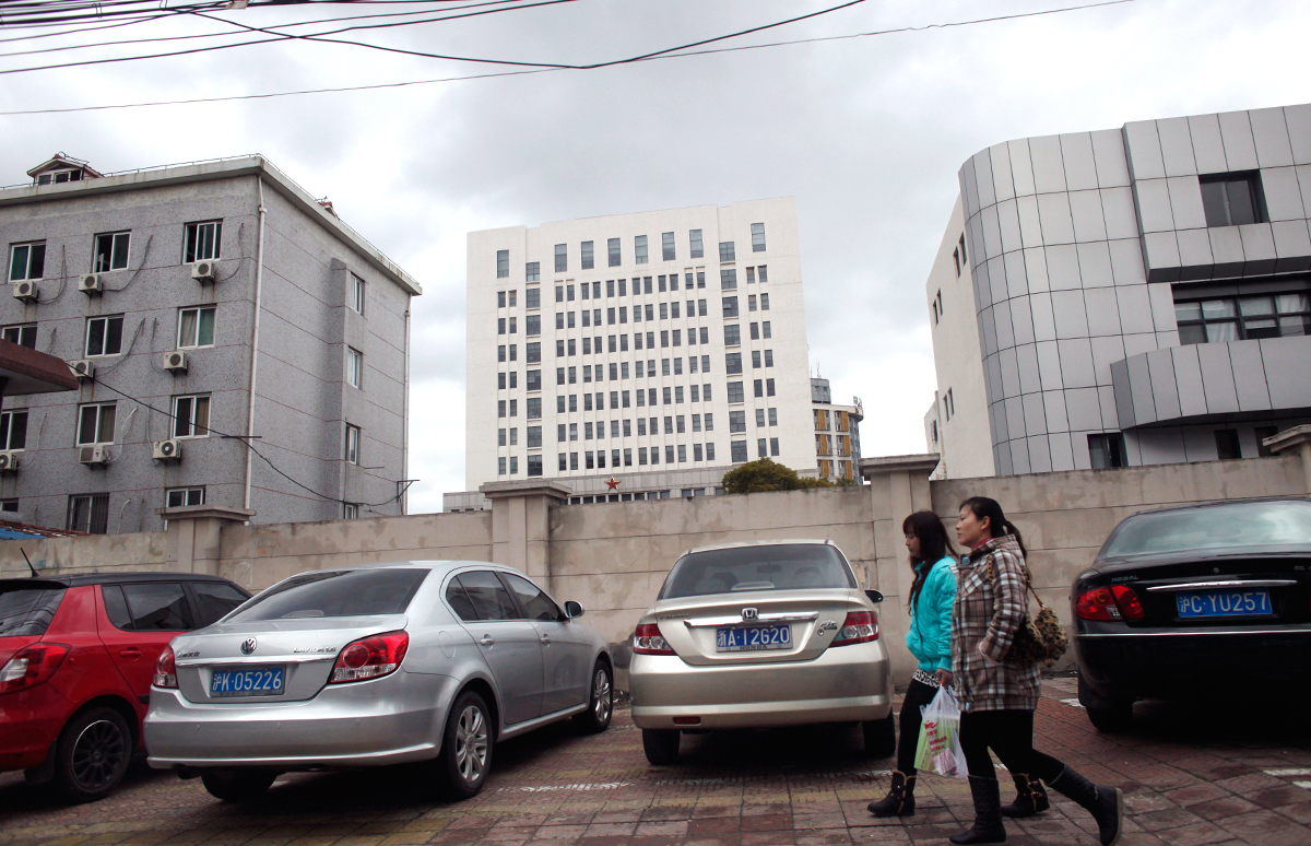 People walk past 'Unit 61398' in Shanghai, the unit believed to be behind a series of hacking attacks.