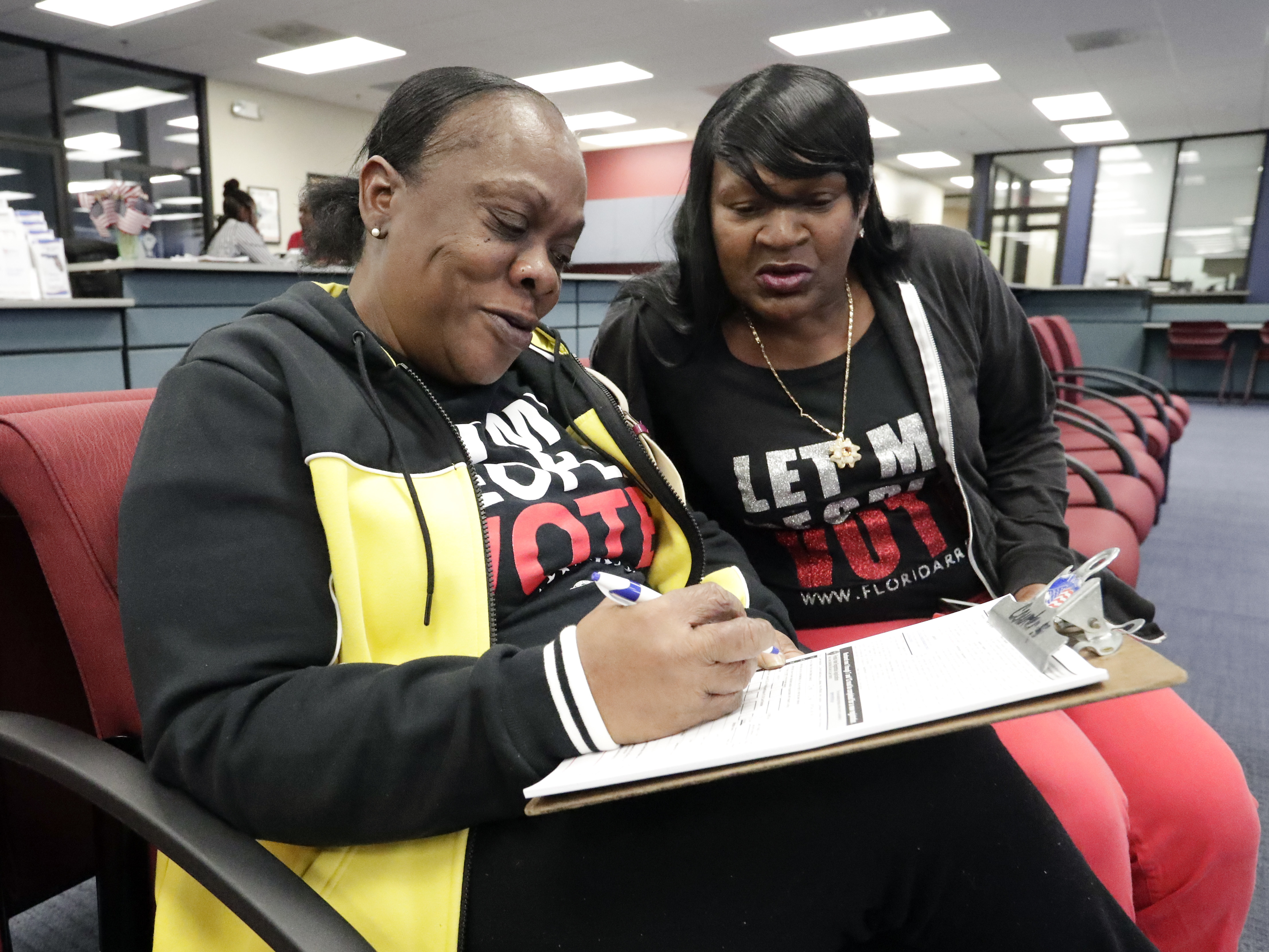 Former felon Yolanda Wilcox, left, fills out a voter registration form as her best friend Gale Buswell looks on at the Supervisor of Elections office Tuesday, Jan. 8, 2019, in Orlando, Fla.