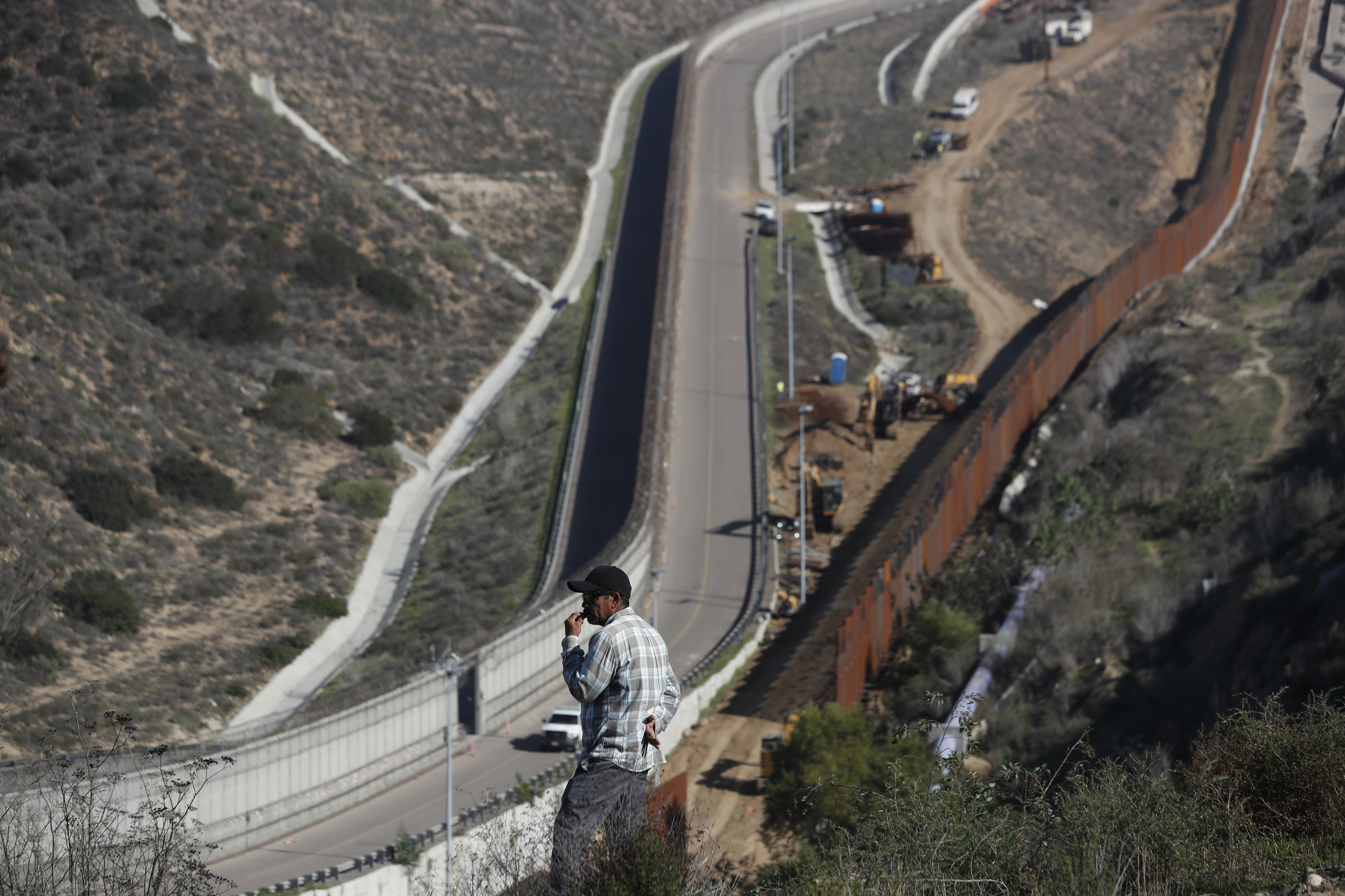A man looks out at the U.S. border where workers are replacing parts of the U.S. border wall for a higher one, in Tijuana, Mexico, Dec. 19, 2018.