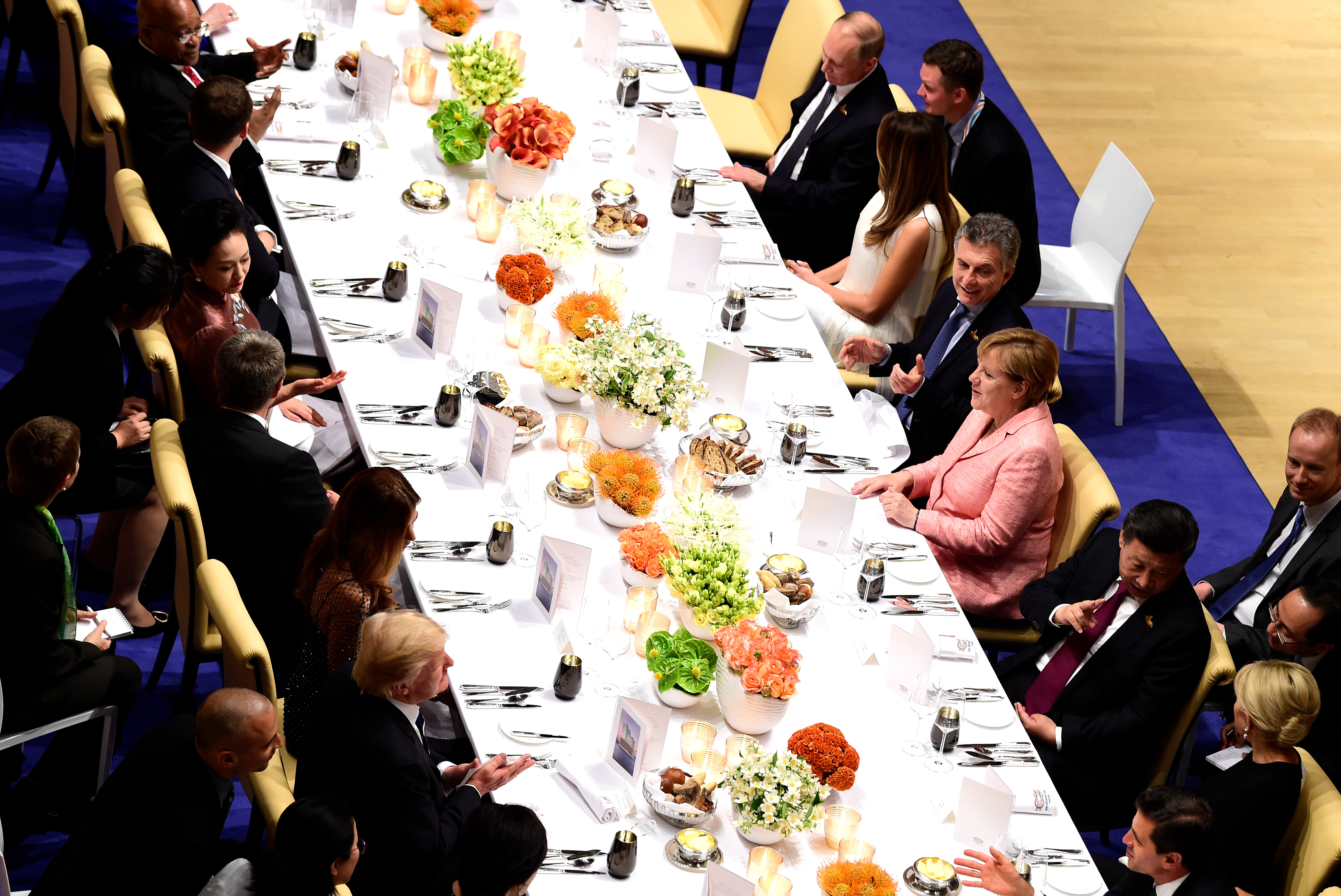 FILE - German Chancellor Angela Merkel, center right, flanked by, from left, Russia's President Vladimir Putin, U.S. first lady Melania Trump, Argentinia's President Mauricio Macri and China's President Xi Jinping, attends a banquet after a concert a...