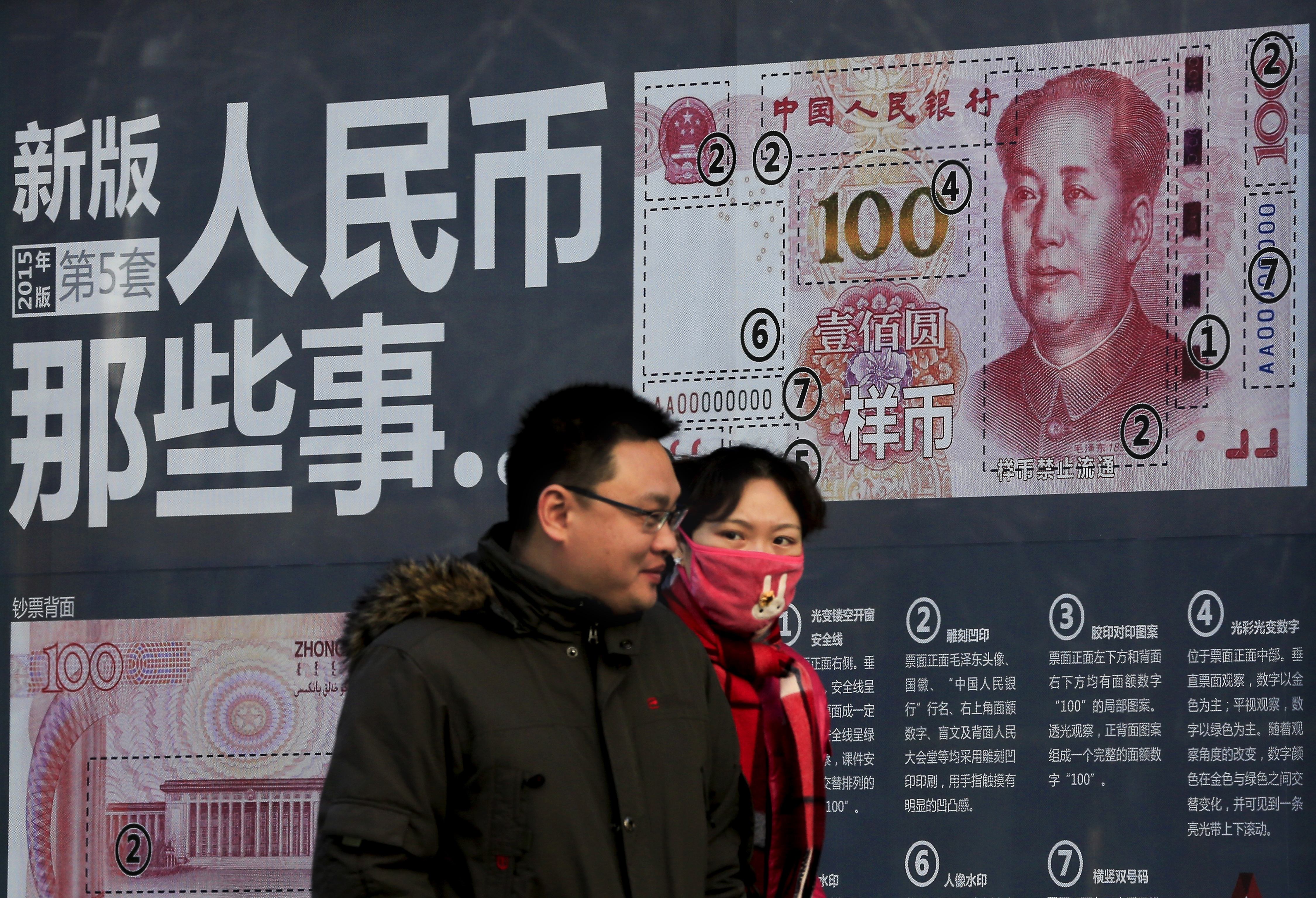 A couple walk past a display showing the security features of the new 100 Yuan note in Beijing, Monday, Jan. 11, 2016.