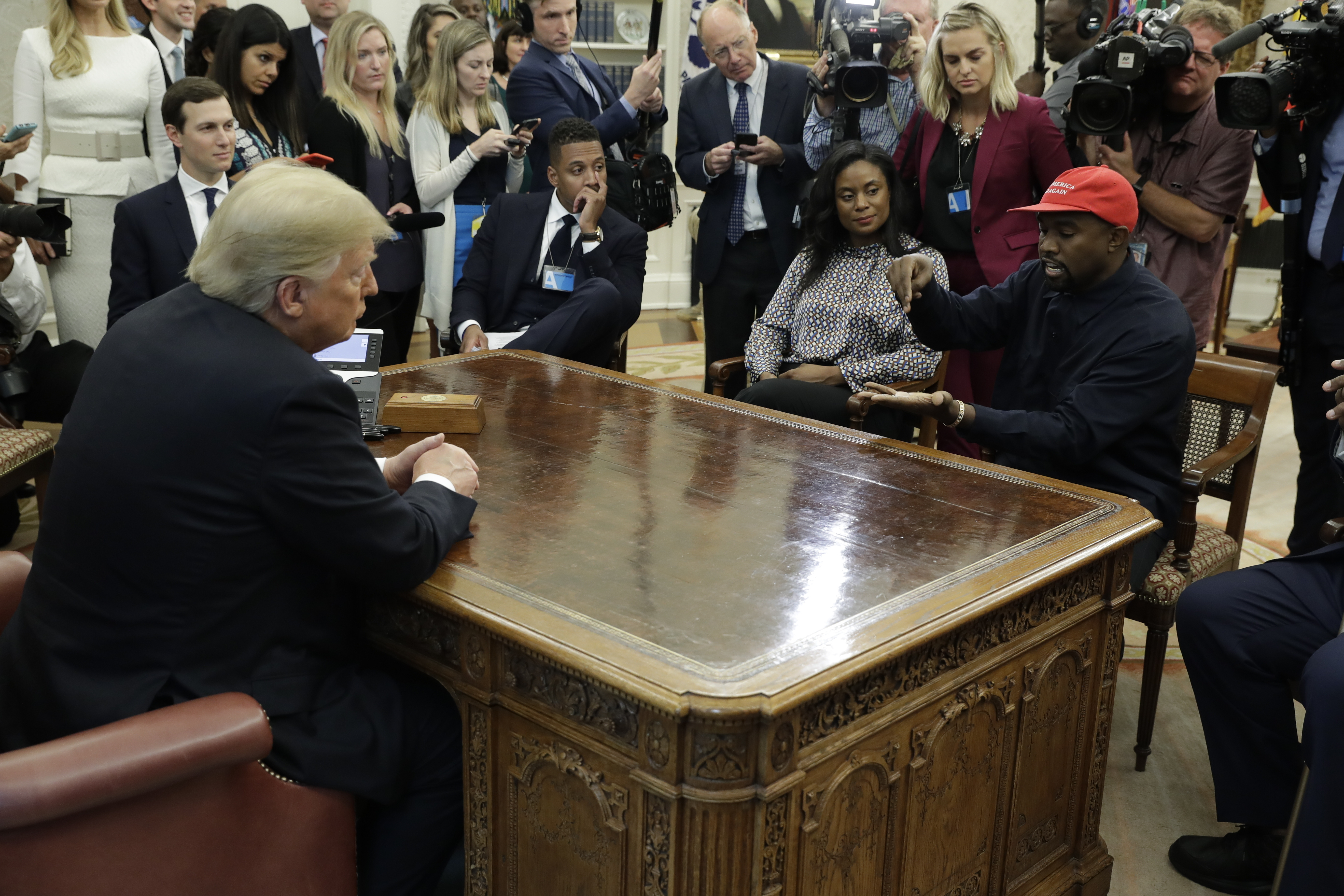 Rapper Kanye West (R) speaks to President Donald Trump and others in the Oval Office of the White House, Oct. 11, 2018, in Washington.