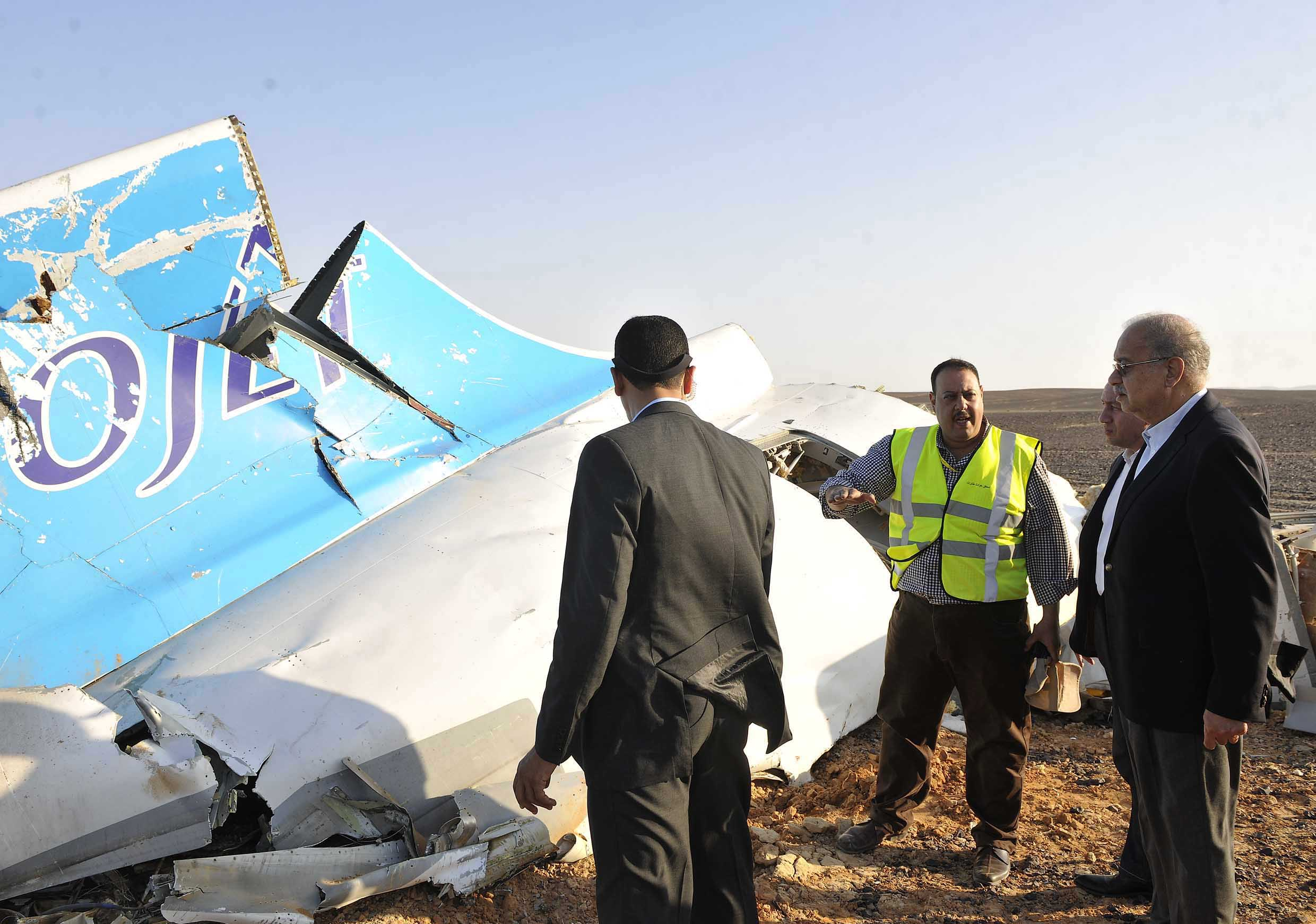 In this image released by the Prime Minister's office, Sherif Ismail, right, looks at the remains of a crashed passenger jet in Hassana Egypt, Friday, Oct. 31, 2015.