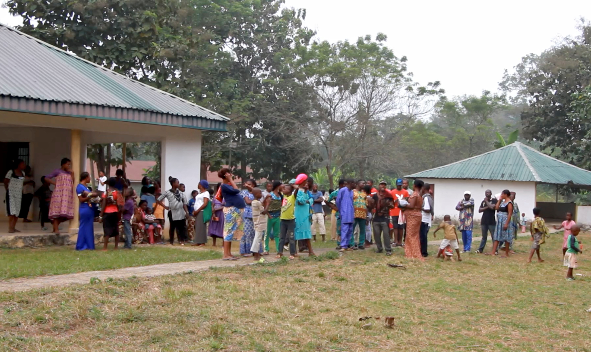 A still image taken from a video shot Dec. 9, 2017, shows Cameroonian refugees standing outside a center in Agbokim Waterfalls village, which is near the Cameroon-Nigeria border.