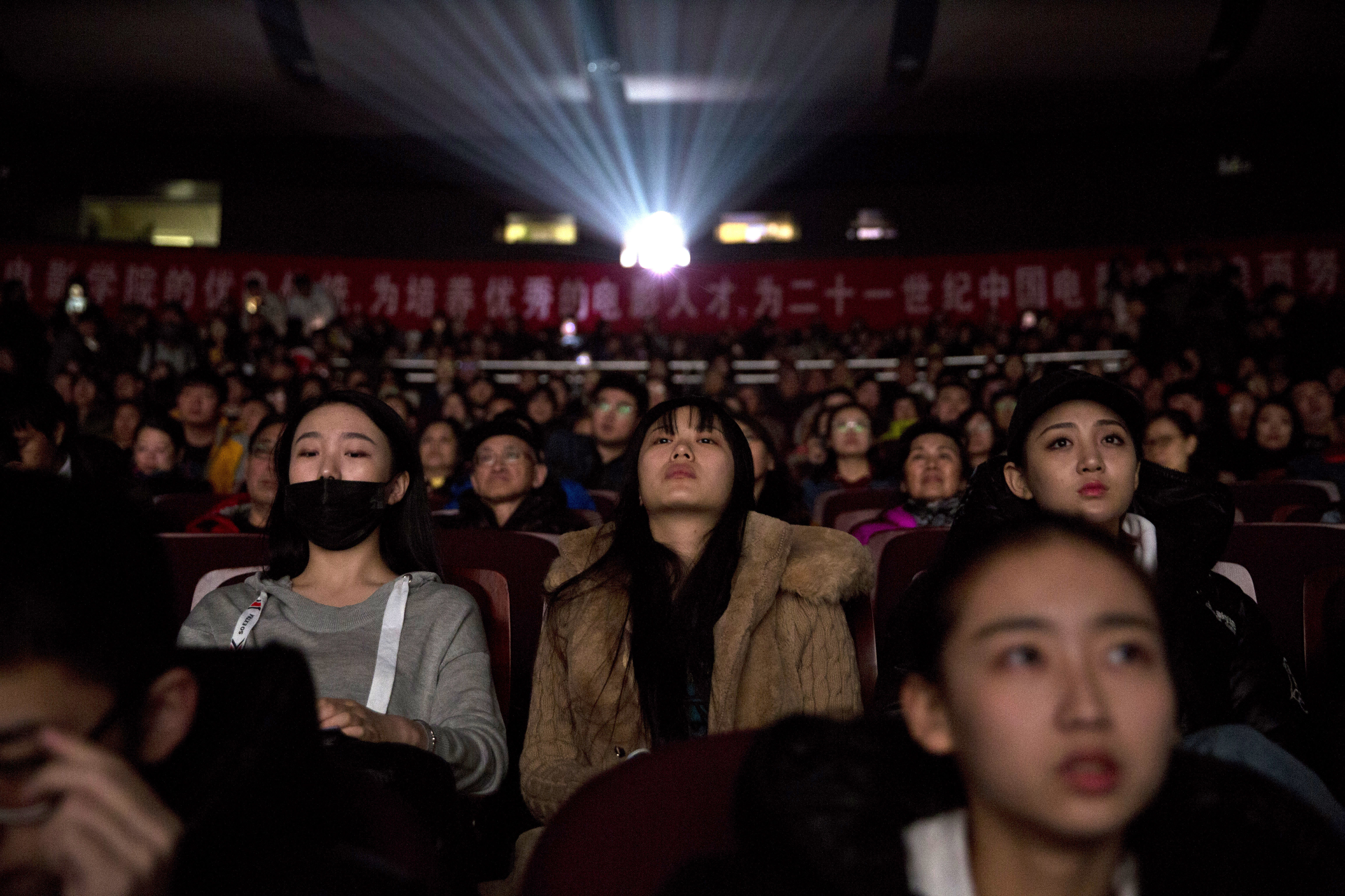 """Audience members watch a screening of the state-backed documentary """"Amazing China"""" at the Beijing Film Academy in Beijing, China, March 22, 2018."""