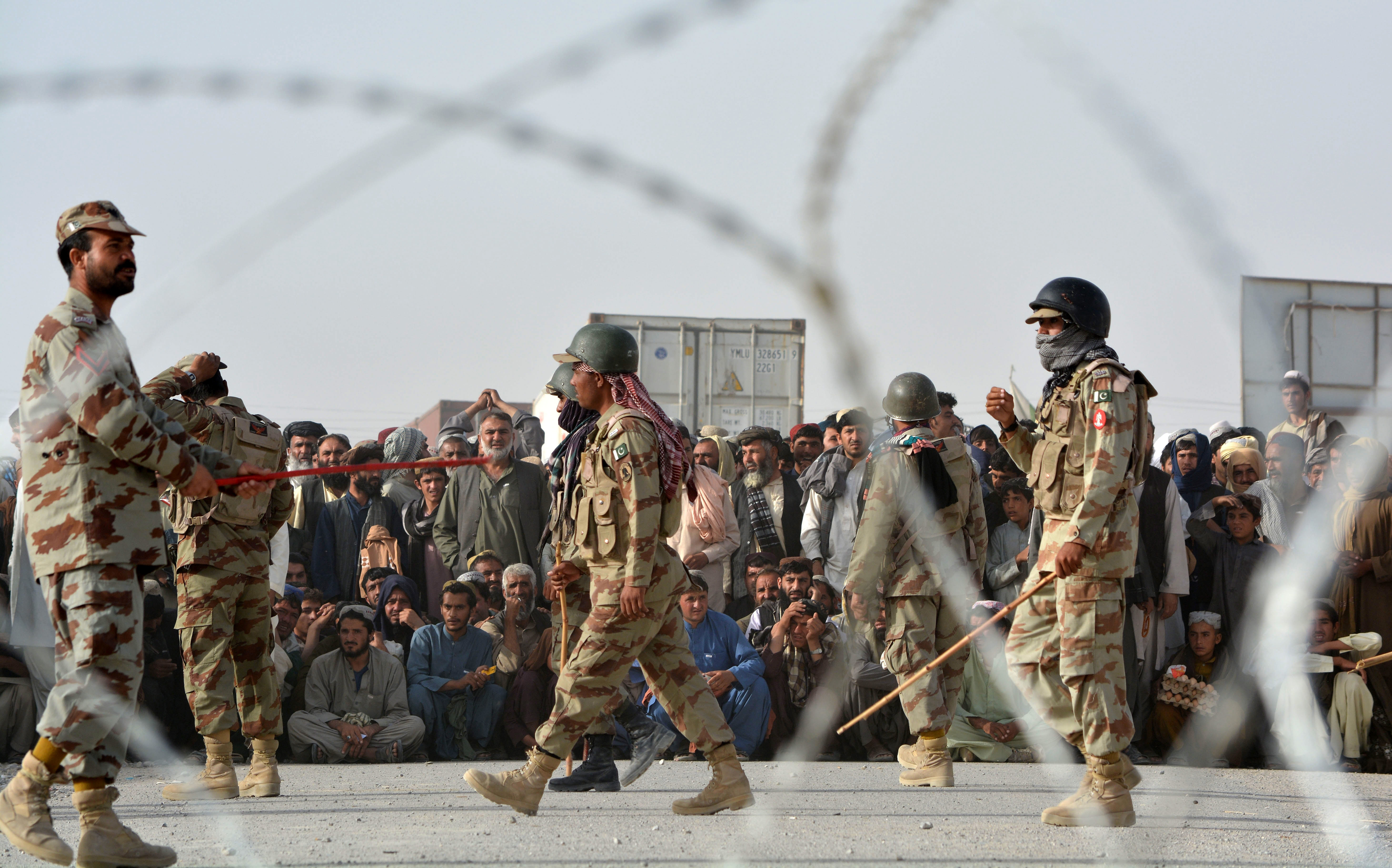 FILE - People wait to cross into Afghanistan at the Pakistani border post Chaman, Sept. 1, 2016. Afghanistan opposes a new Pakistani flag ceremony at the key border crossing between the countries.