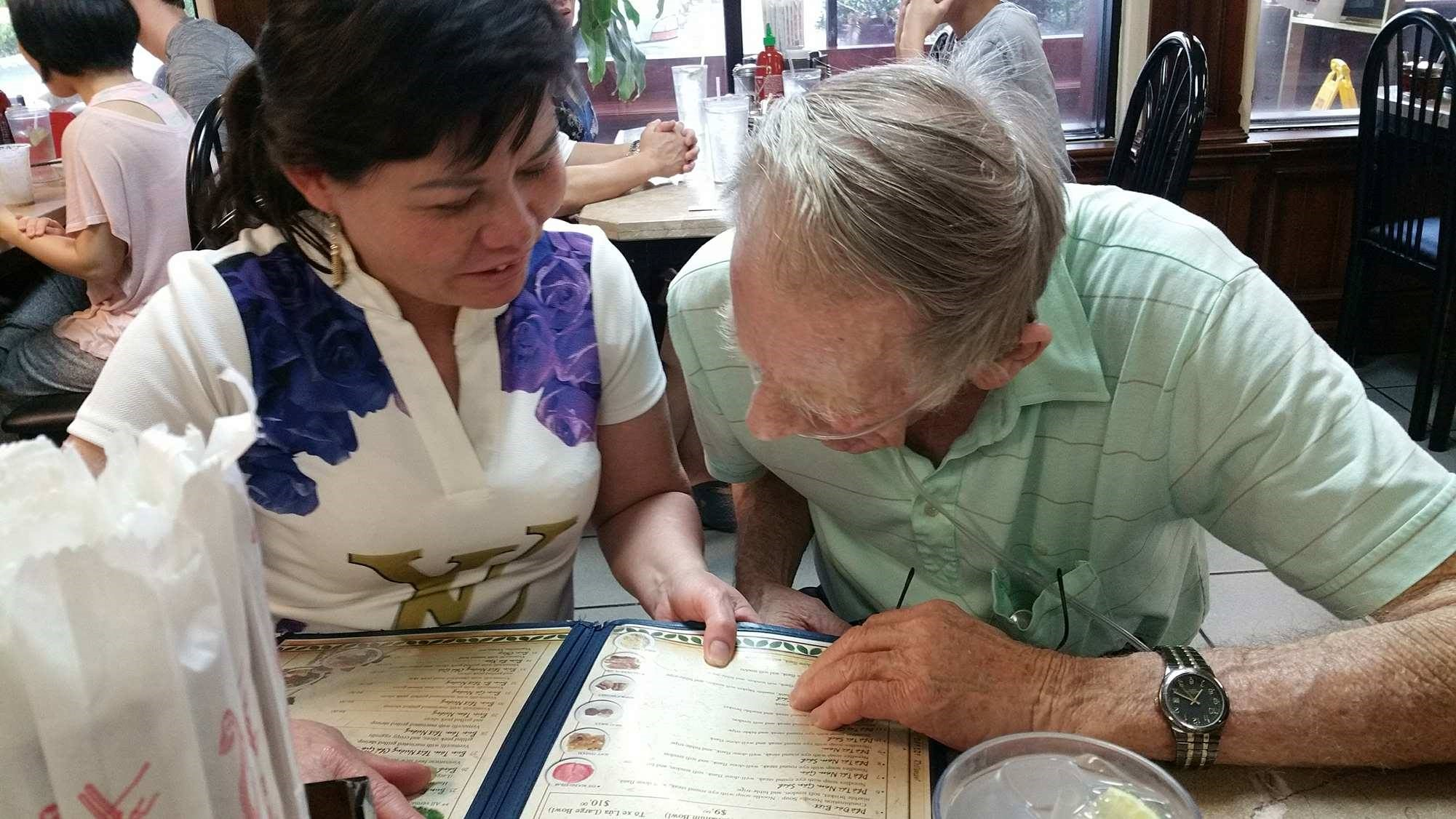 Nguyễn Thị Kim Nga, left, helps her father, Gary Wittig, decide on Vietnamese dinner during their first meeting in Atlanta.