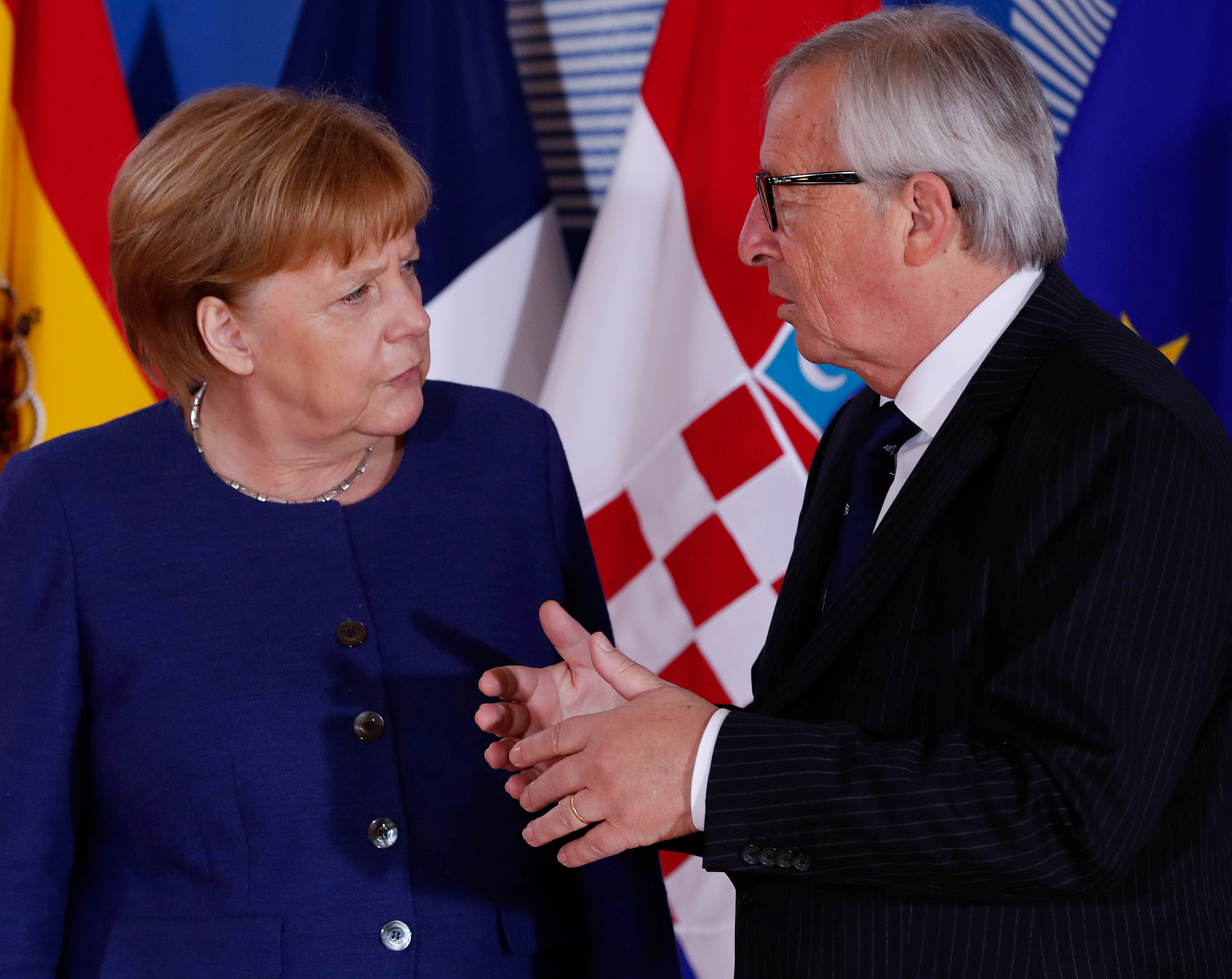 German Chancellor Angela Merkel is welcomed by EU President Jean-Claude Juncker at the start of an emergency European Union leaders summit on immigration at the EU Commission headquarters in Brussels, Belgium, June 24, 2018.