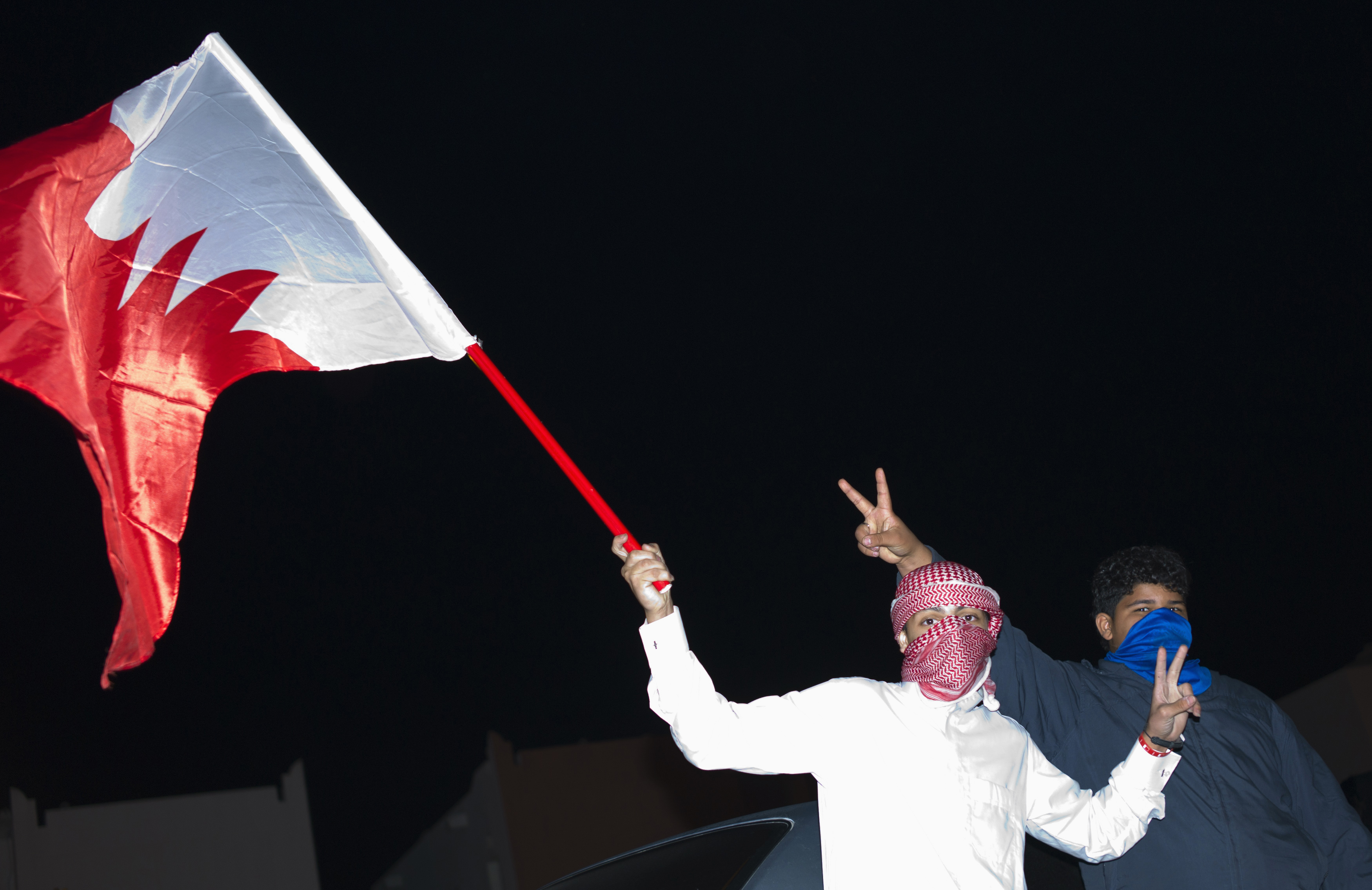 FILE - Sunni protesters wave a Bahraini flag as they protest, demanding the government end chaos in their country, in Hamad Town south of Manama, Dec. 24, 2011.