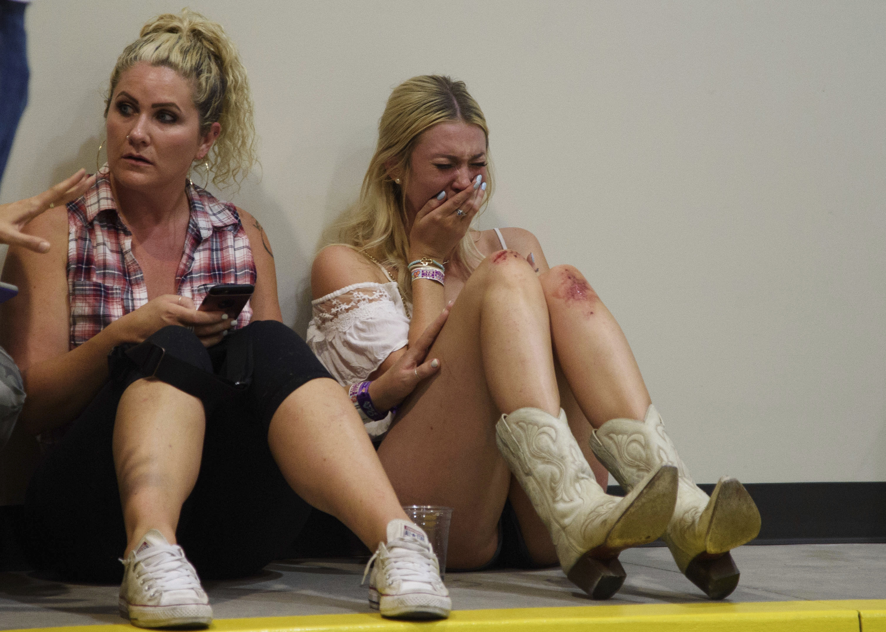 A woman cries while hiding inside the Sands Corporation plane hangar after a mass shooting in which dozens were killed at the Route 91 Harvest country festival on Oct. 1, 2017, in Las Vegas.