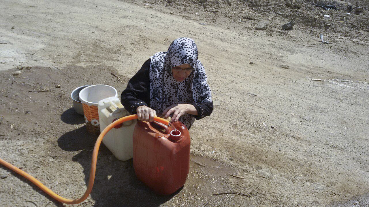 An Iraqi woman gathers water in a neighborhood in central Fallujah, Iraq as Iraqi counterterrorism forces battle Islamic State militants on the southern edge of the city on May 31, 2016.