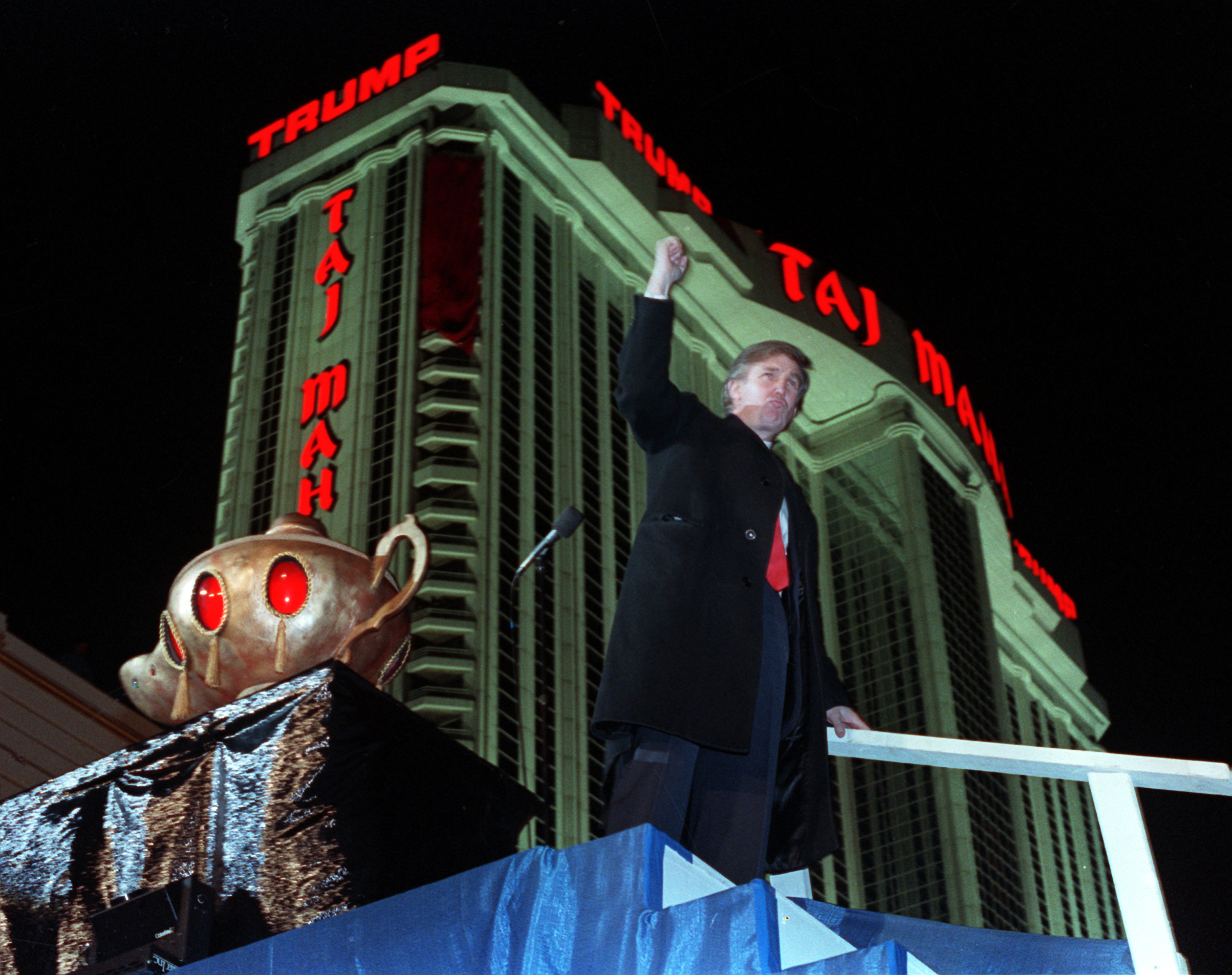 Donald Trump ascends the stairs with his fist raised from the genie's lamp after opening the Trump Taj Mahal Casino Resort in a spectacular show of fireworks and laser lights in Atlantic City, N.J., on April 5, 1990.  Behind Trump is the 42-story hot...