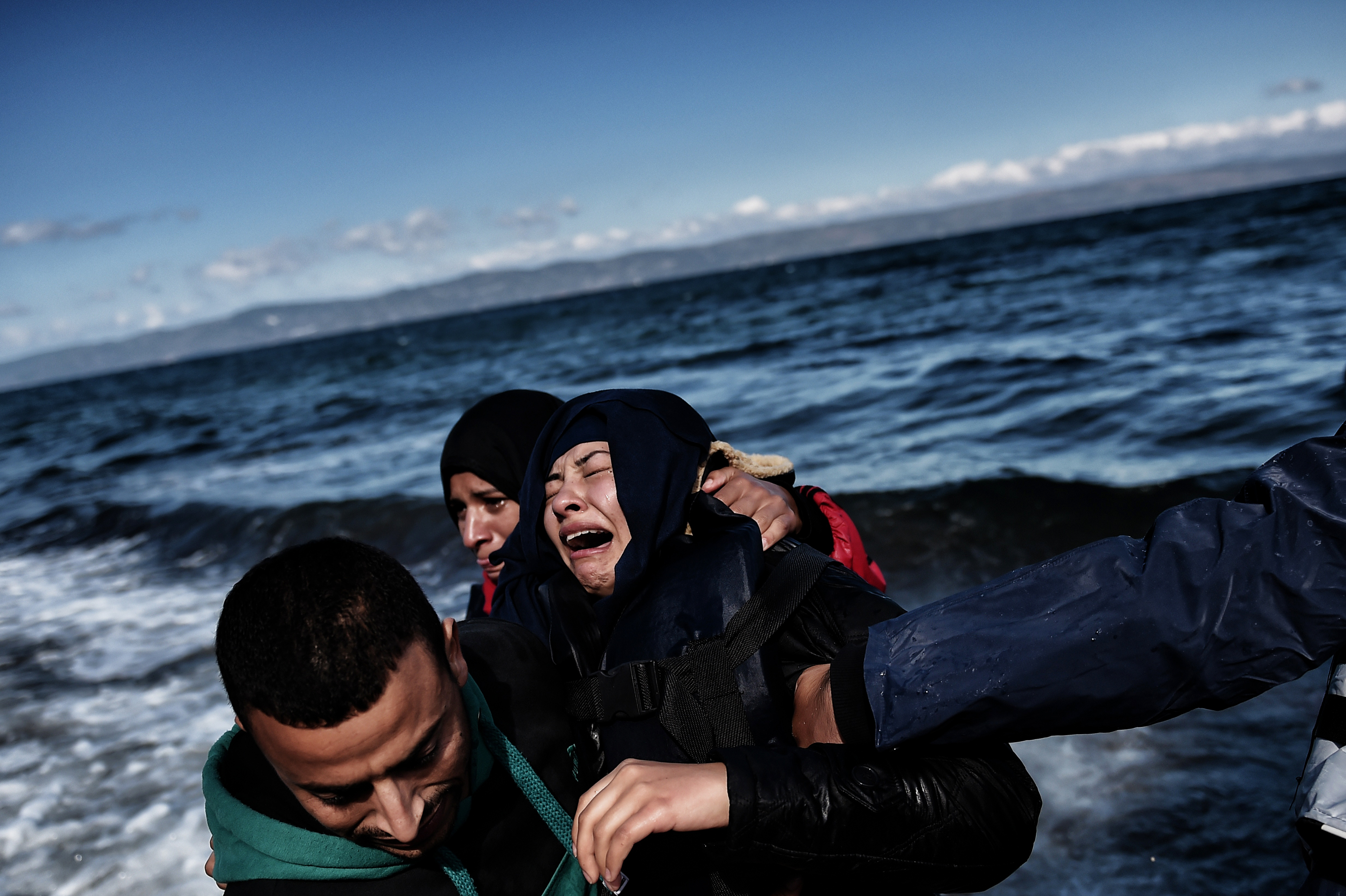 A man comforts a woman upon arrival with other refugees and migrants on the Greek island of Lesbos on October 25, 2015 after they crossed the Aegean sea from Turkey.