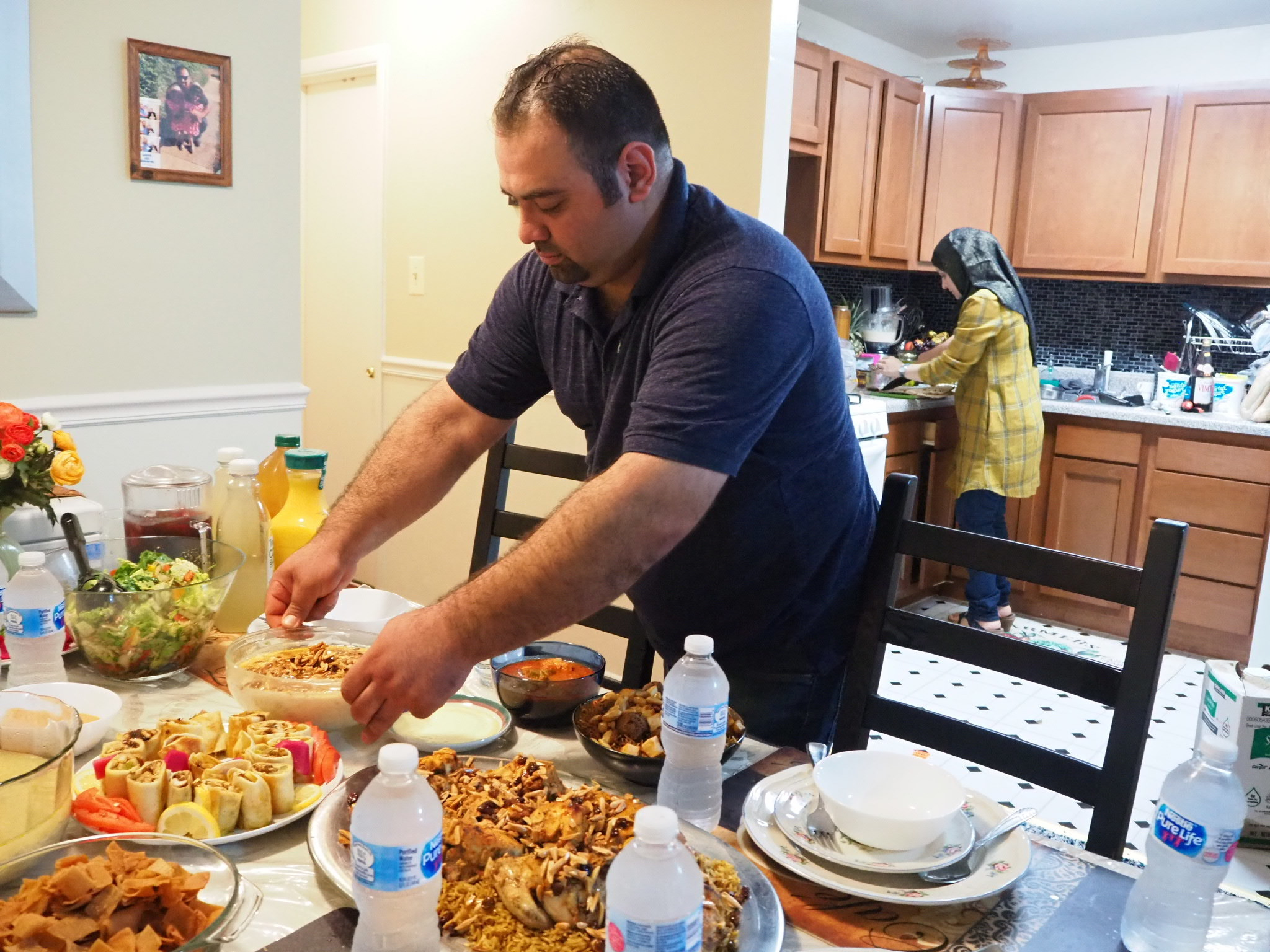 FILE - Syrian refugee Majed Abdalraheem, 29, sets the table at his home in Riverdale, Md., as he and his wife, Walaa Jadallah, prepare for the iftar meal during Ramadan, May 25, 2018.