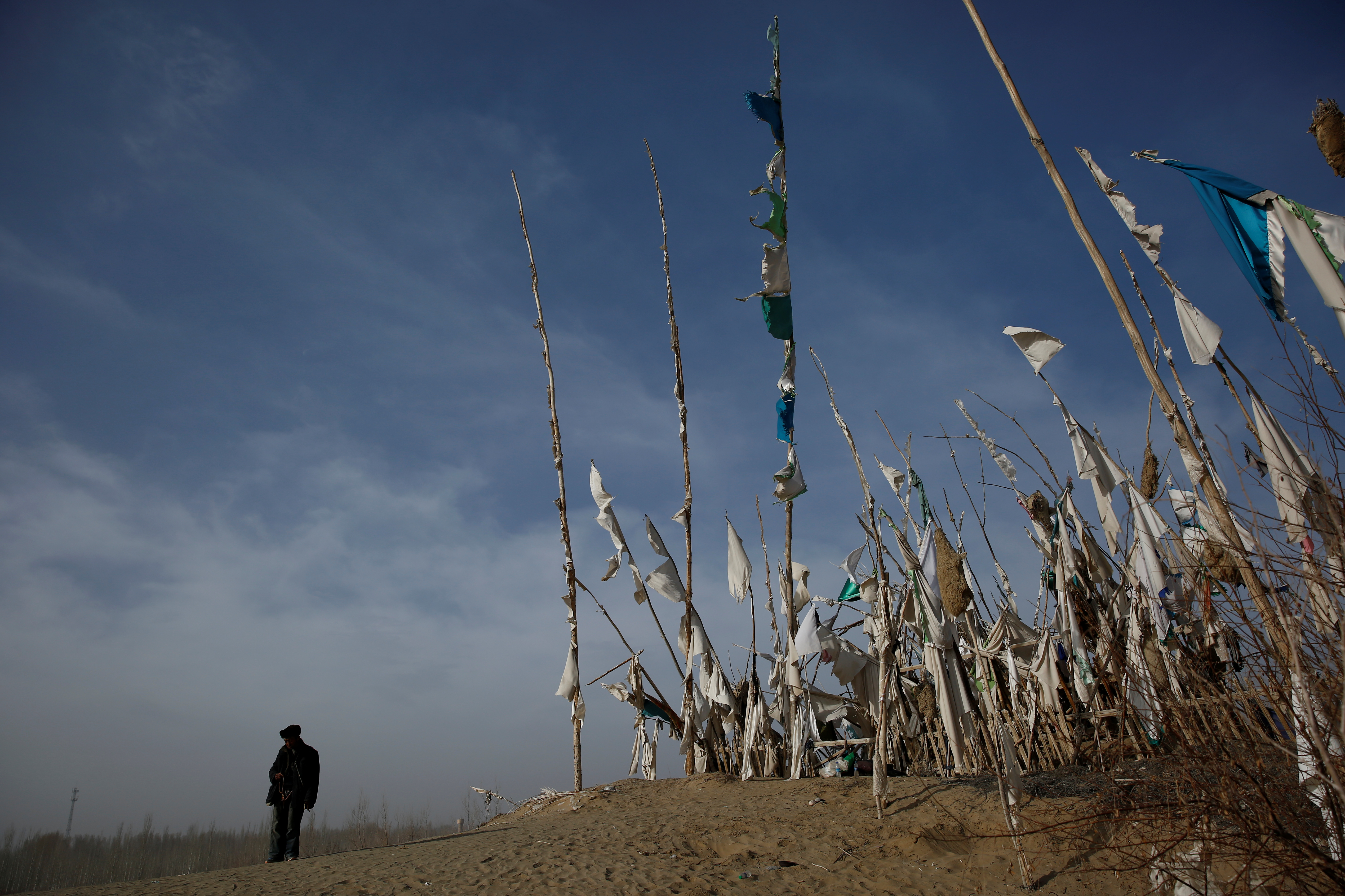 An ethnic Uighur stands in front of a grave at the cemetry surrounding the tomb of Imam Asim in the Taklamakan Desert outside the village of Jiya near Hotan, Xinjiang Uighur Autonomous Region, China, March 21, 2017.