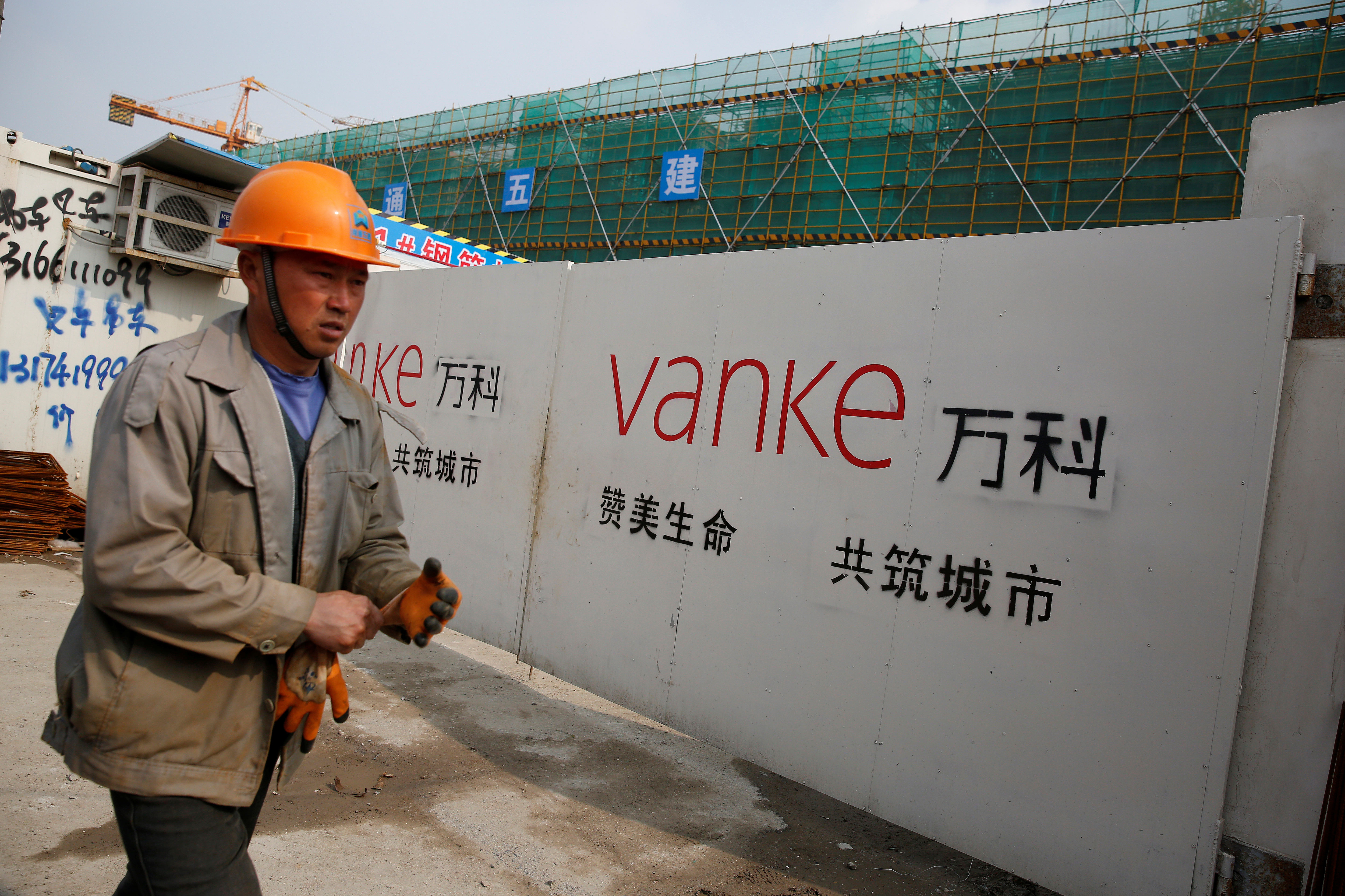 A person walks past by a gate with a sign of Vanke at a construction site in Shanghai, China, March 21, 2017.