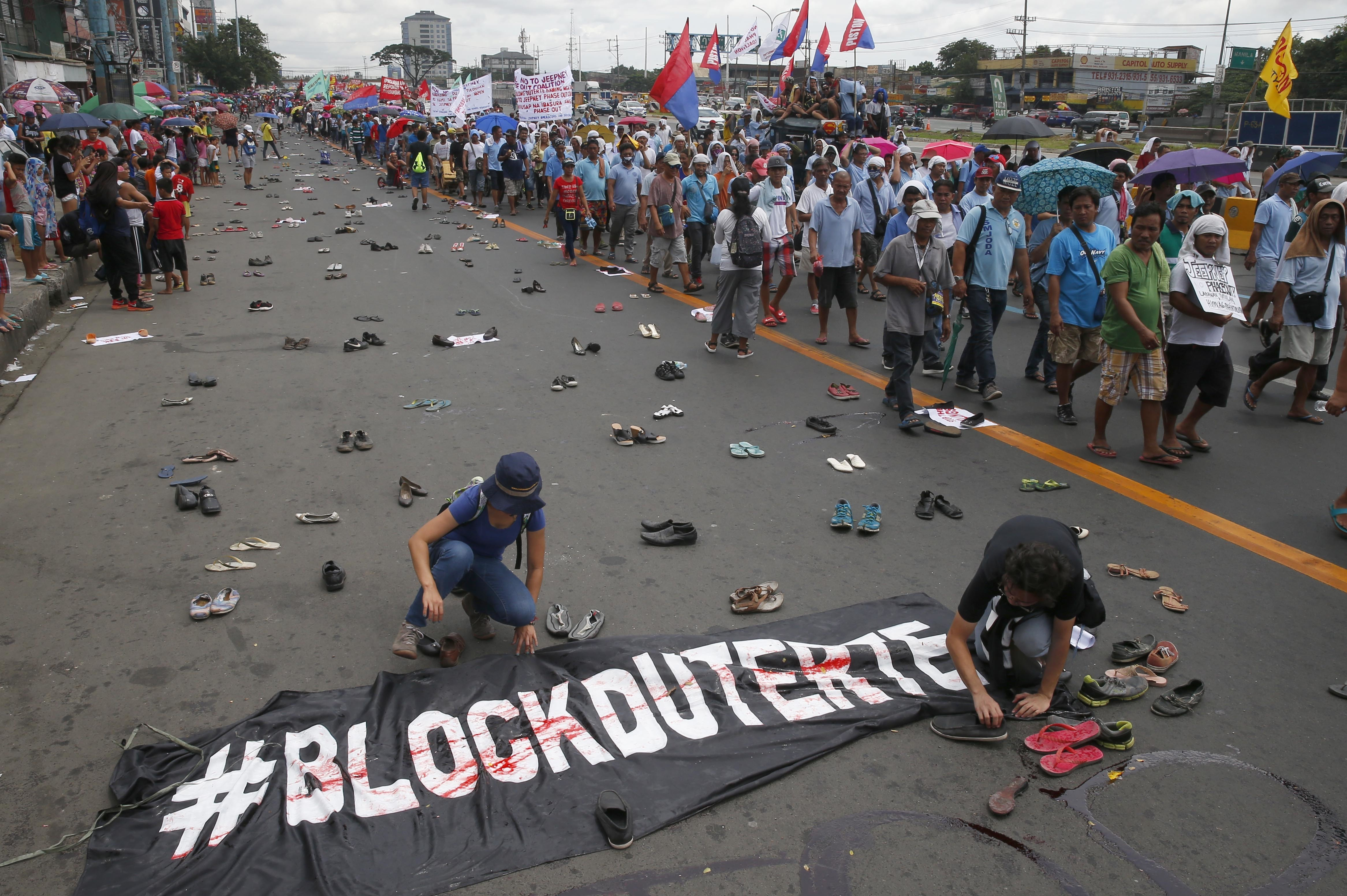Protesters scatter pairs of slippers and shoes to symbolize victims killings in the so-called war on drugs of President Rodrigo Duterte as others march towards the Lower House to coincide with Duterte's second state of the nation address Monday, July...