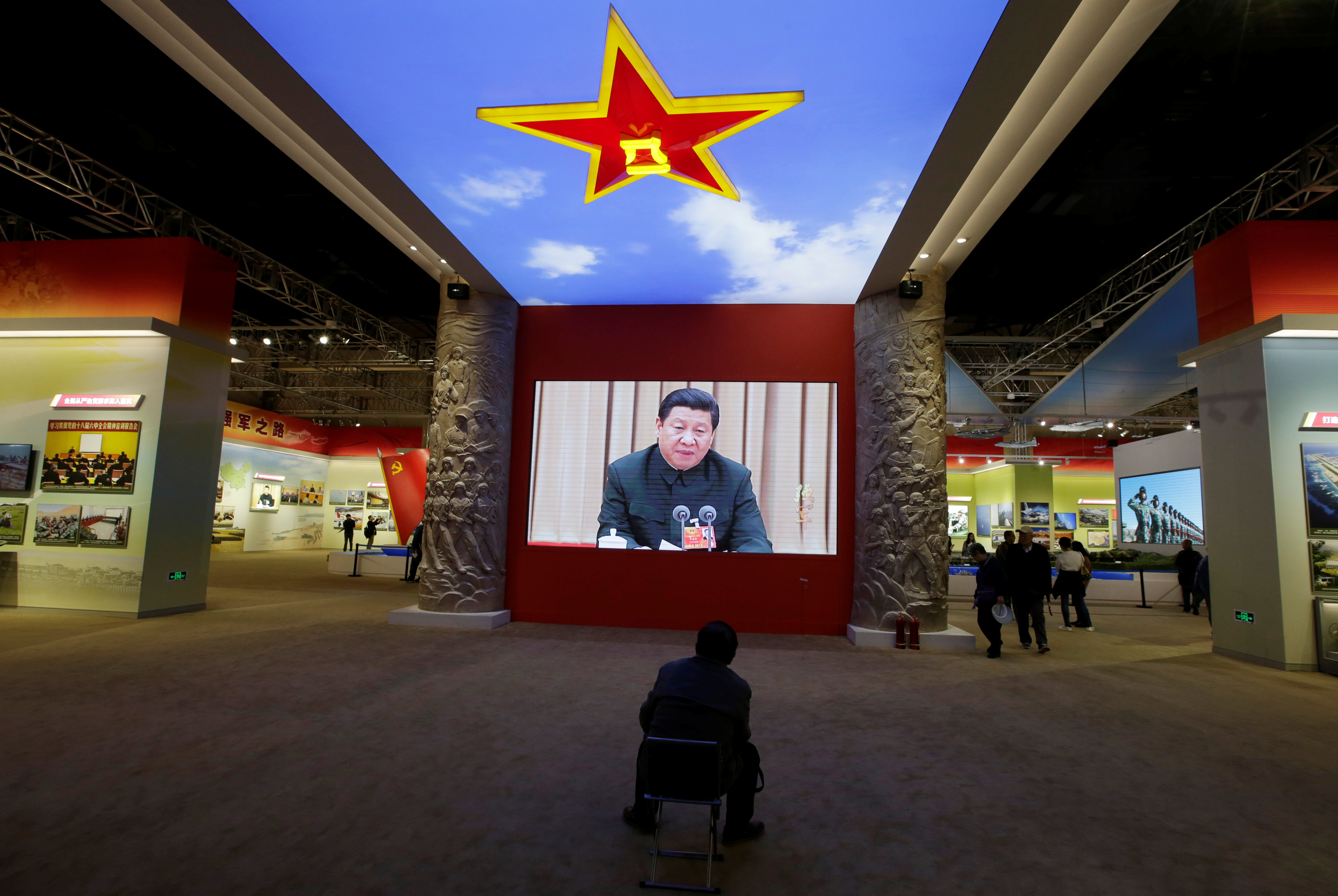 A visitor watches a video showing Chinese President Xi Jinping