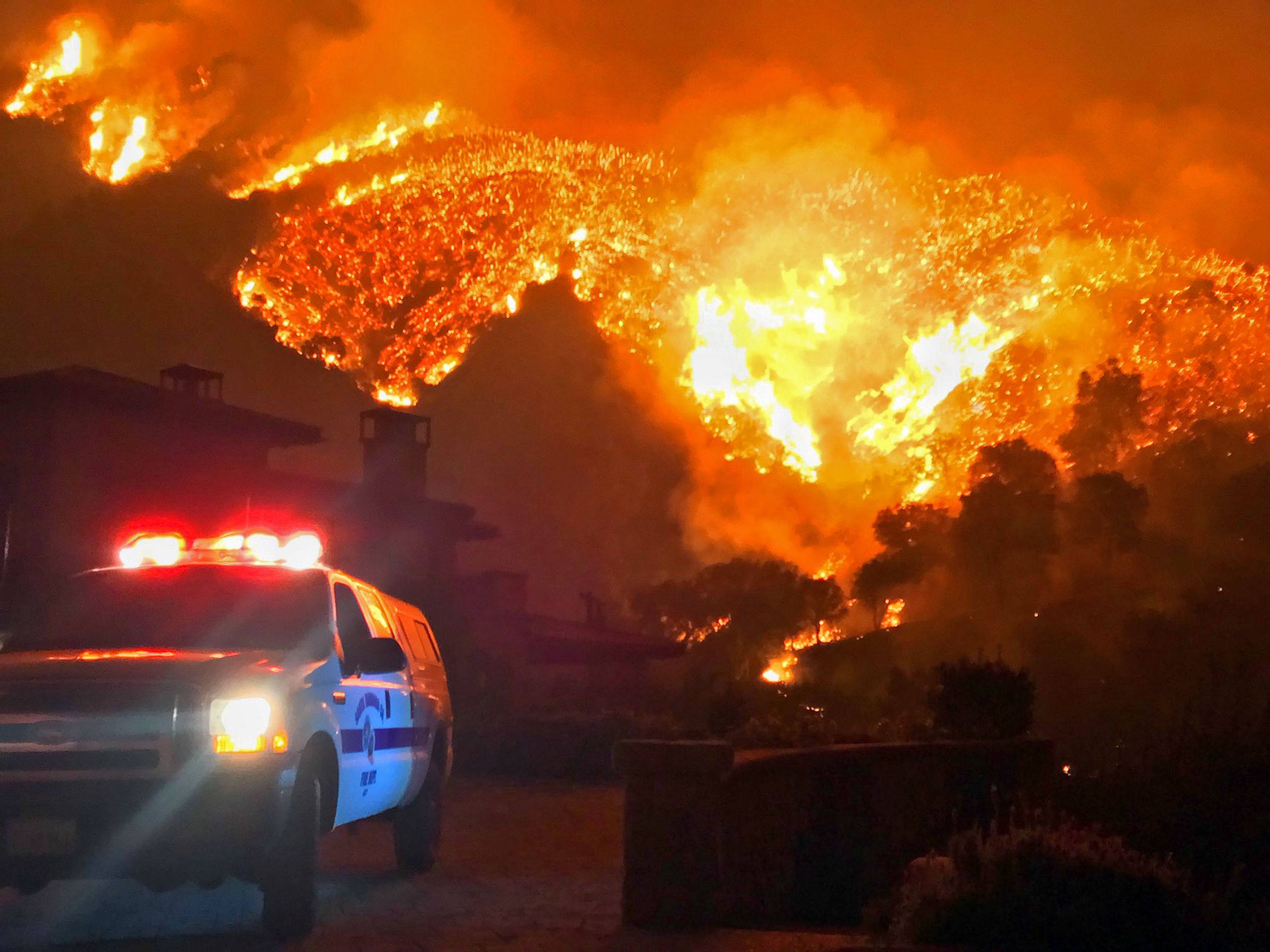 In this photo provided by the Santa Barbara County Fire Department, fire burns canyons and ridges above Bella Vista Drive near Romero Canyon as the fight to contain a wildfire continues in Montecito, Calif., Tuesday, Dec. 12, 2017.