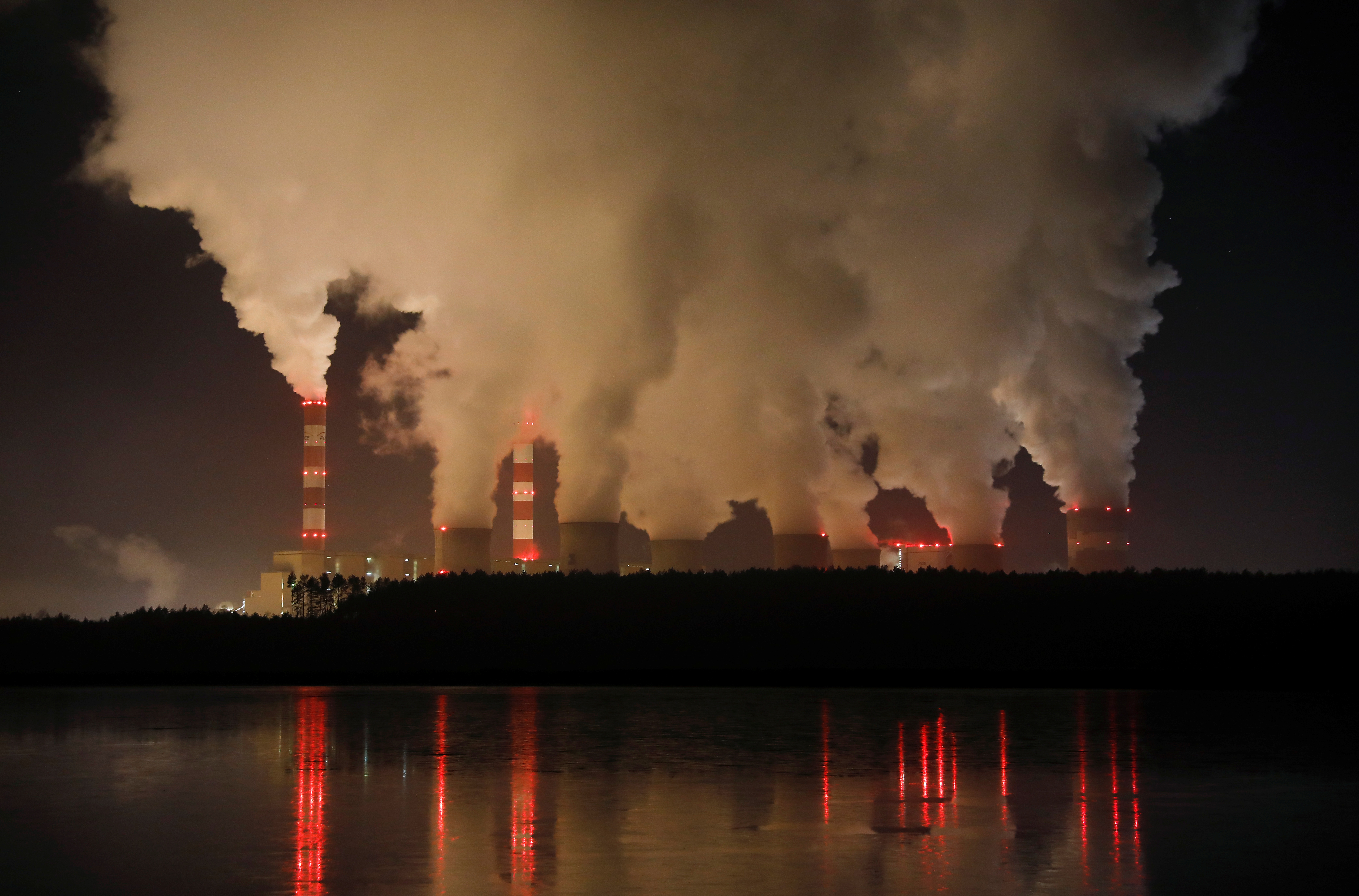 FILE - Smoke and steam billows from Belchatow Power Station, Europe's largest coal-fired power plant, operated by PGE Group, at night near Belchatow, Poland, Dec. 5, 2018.