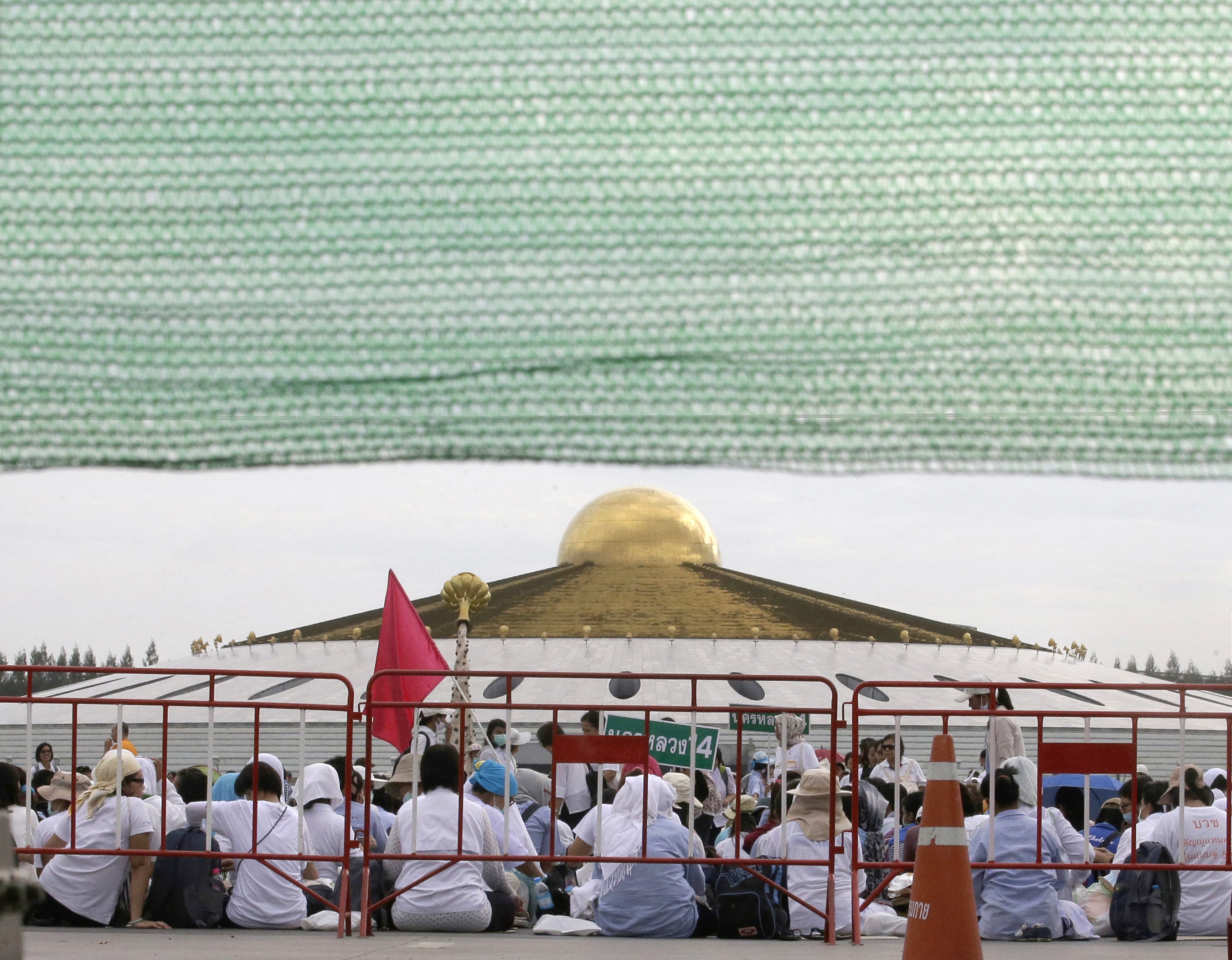 Buddhist monks and devotees sit outside the Wat Phra Dhammakaya temple in Pathum Thani province, north of Bangkok, Thailand, Thursday, June 16, 2016.