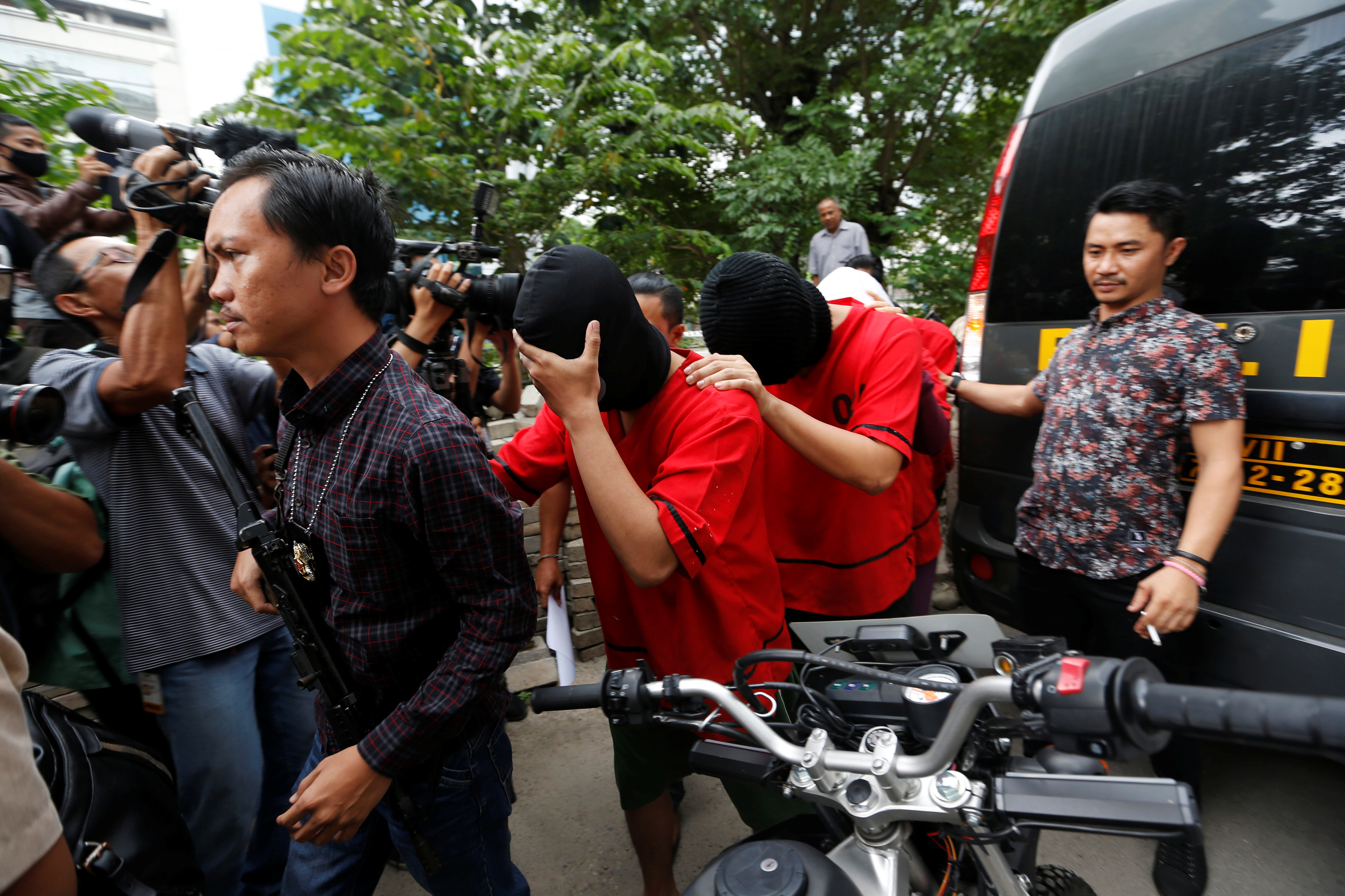 """FILE - A plainclothes policeman holds a rifle as he escorts suspects during a police investigation into a men's club after a weekend raid on what authorities described as a """"gay spa"""" in Jakarta, Indonesia, Oct. 9, 2017."""