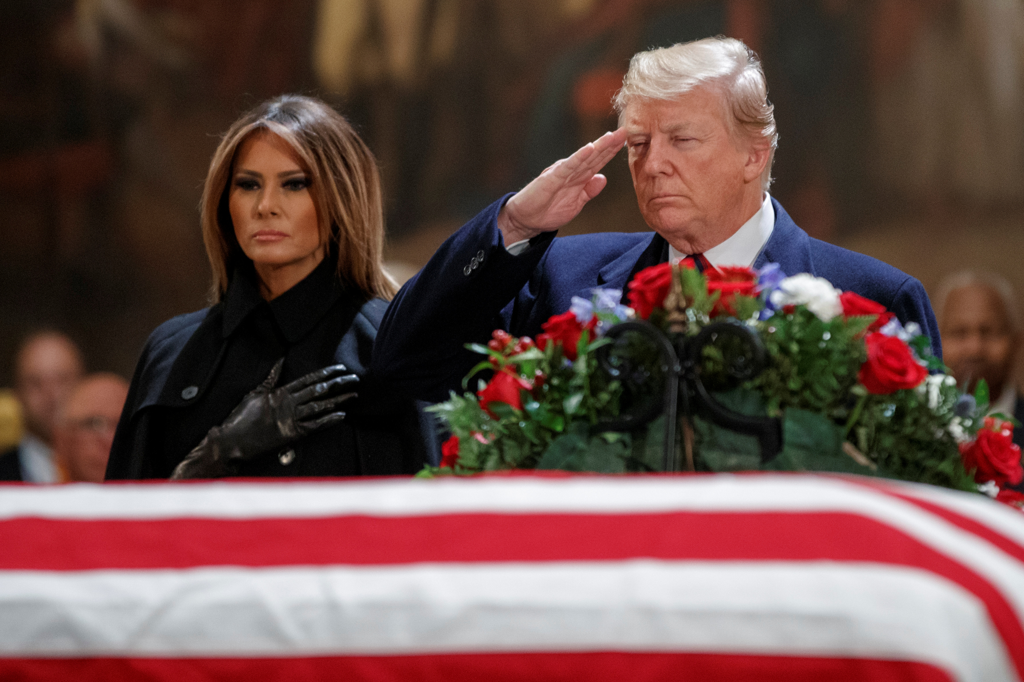 US President Donald J. Trump, with First Lady Melania Trump, salutes the casket containing the body of former US President George H.W. Bush in the Rotunda of the US Capitol in Washington, DC, December 3, 2018.