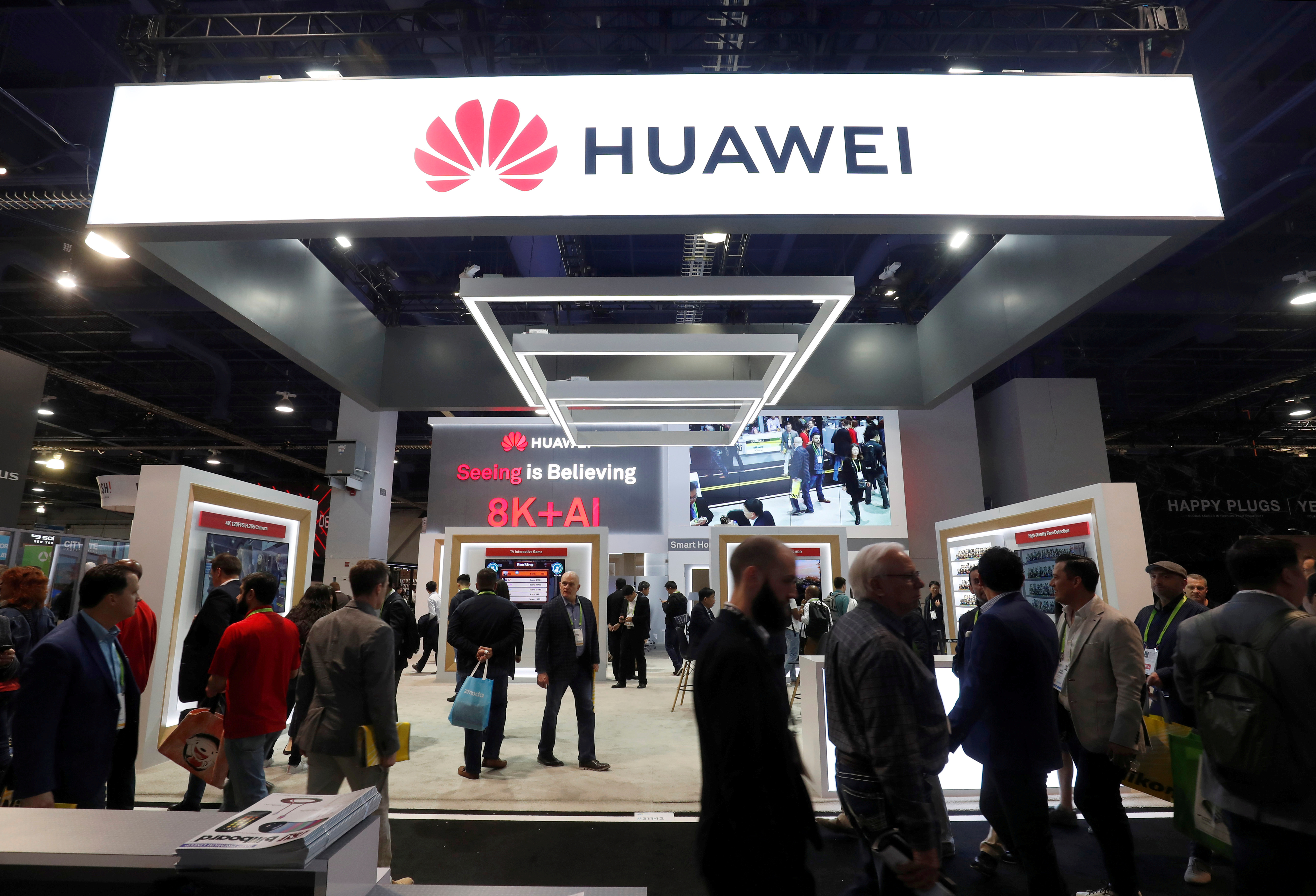 FILE - Attendees pass by a Huawei booth during the 2019 CES in Las Vegas, Nevada, U.S. Jan. 9, 2019.