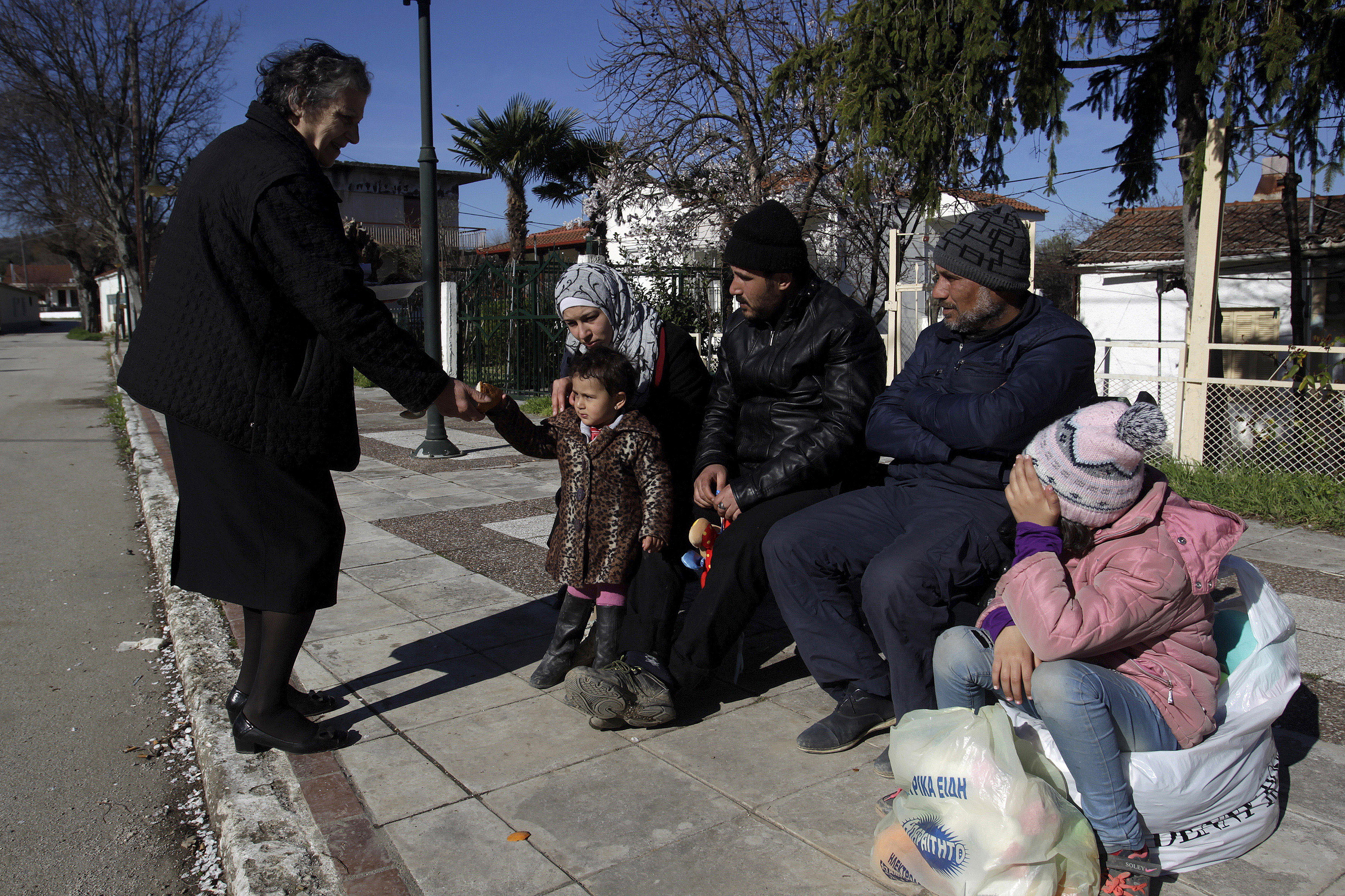 A local (L) offers migrants who are making their way to the Greek-Macedonian border something to eat, at the Greek village of Idomeni, Greece, March 5, 2016.