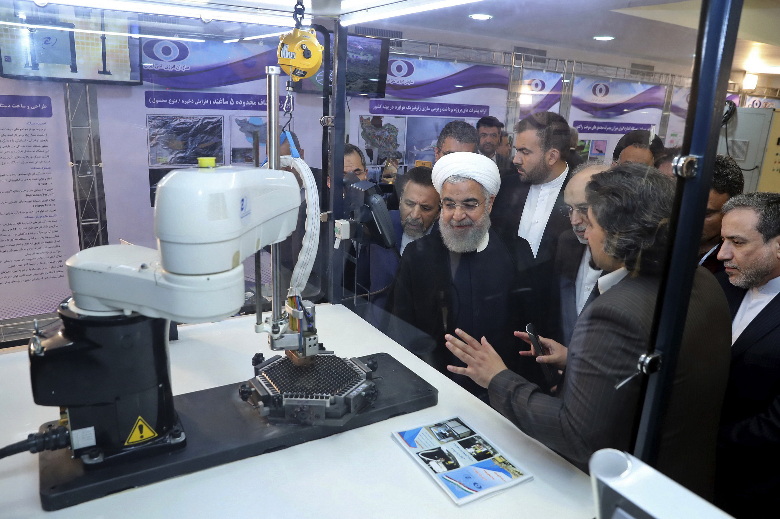 """IIn this photo released by an official website of the office of the Iranian Presidency, President Hassan Rouhani listens to explanations on new nuclear achievements at a ceremony to mark """"National Nuclear Day,"""" in Tehran, Iran, April 9, 2018."""