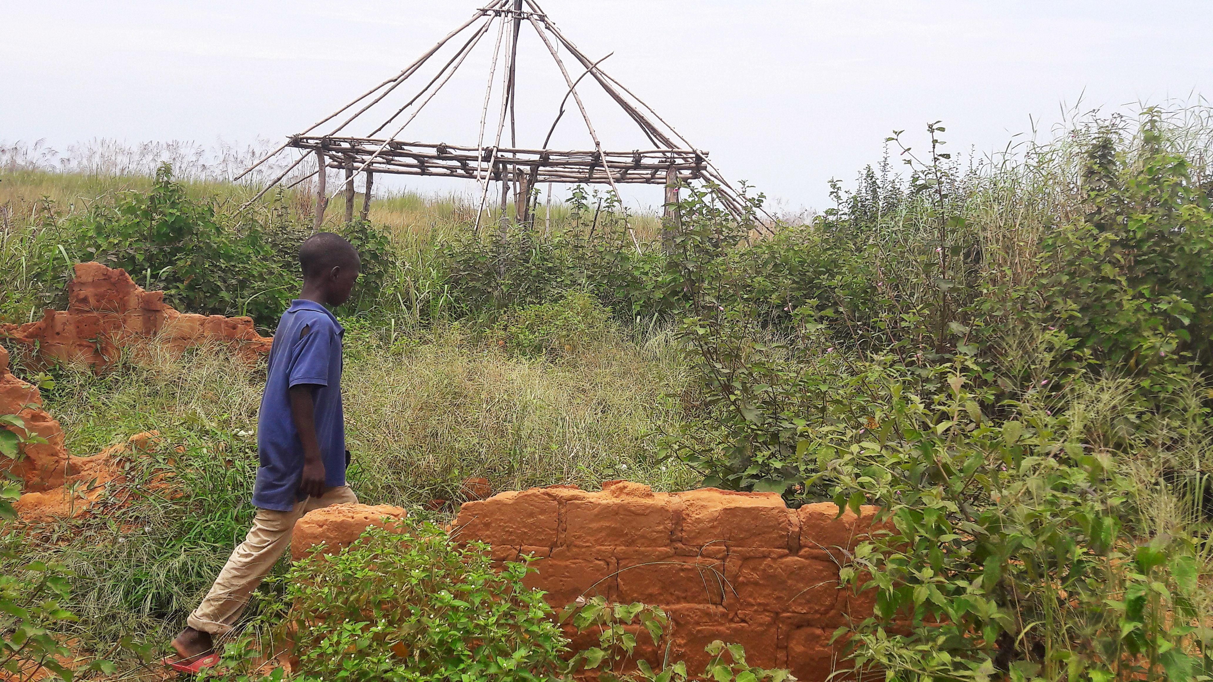FILE - A boy walks past the ruins of the destroyed house of customary chief Kamuina Nsapu, whose death last August sparked months of deadly fighting between the government army and Kamuina Nsapu's militia in Tshimbulu near Kananga, March 11, 2017.