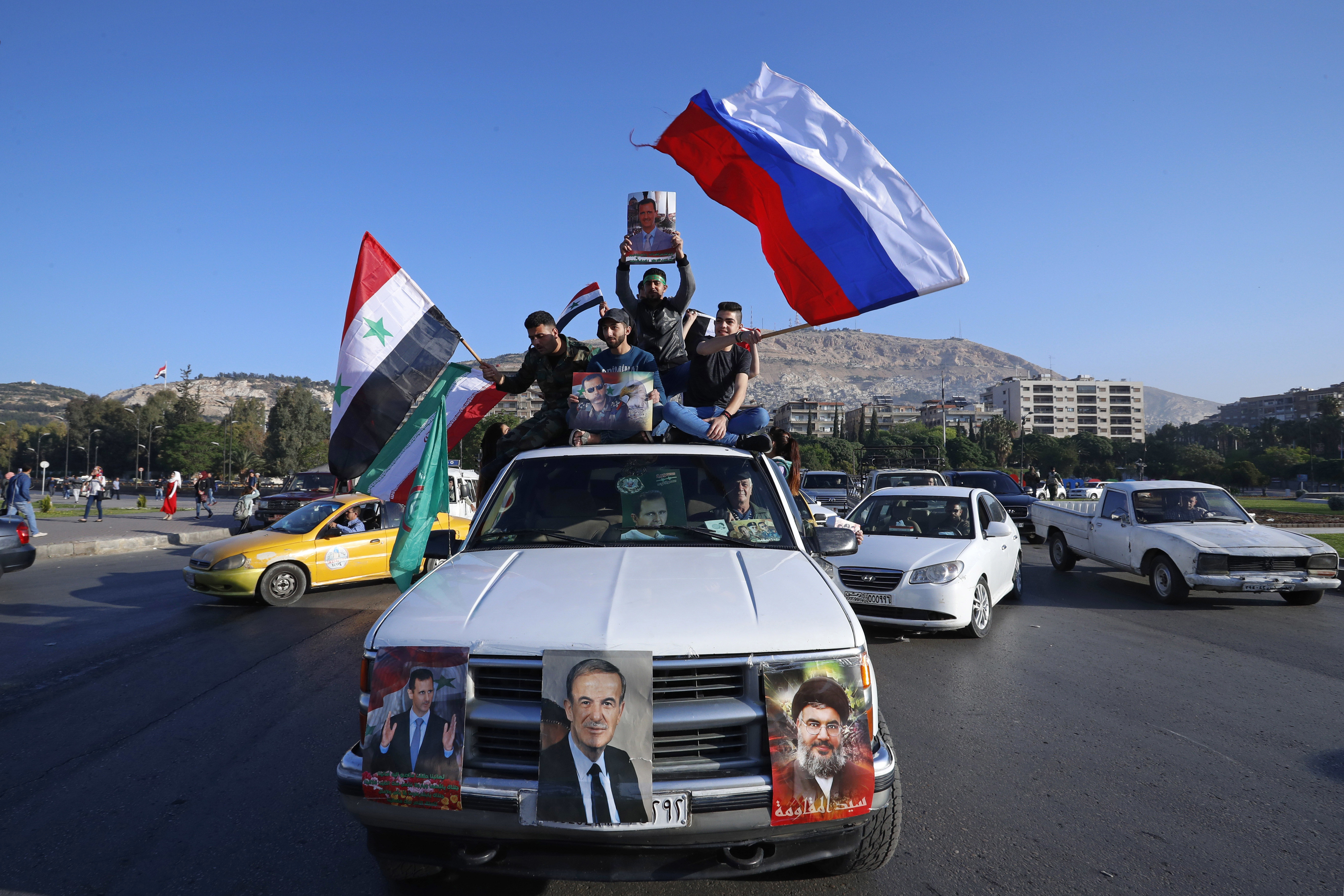 Syrian government supporters wave Syrian, Iranian and Russian flags as they chant slogans against U.S. President Trump during demonstrations following a wave of U.S., British and French military strikes to punish President Bashar al-Assad for suspect...