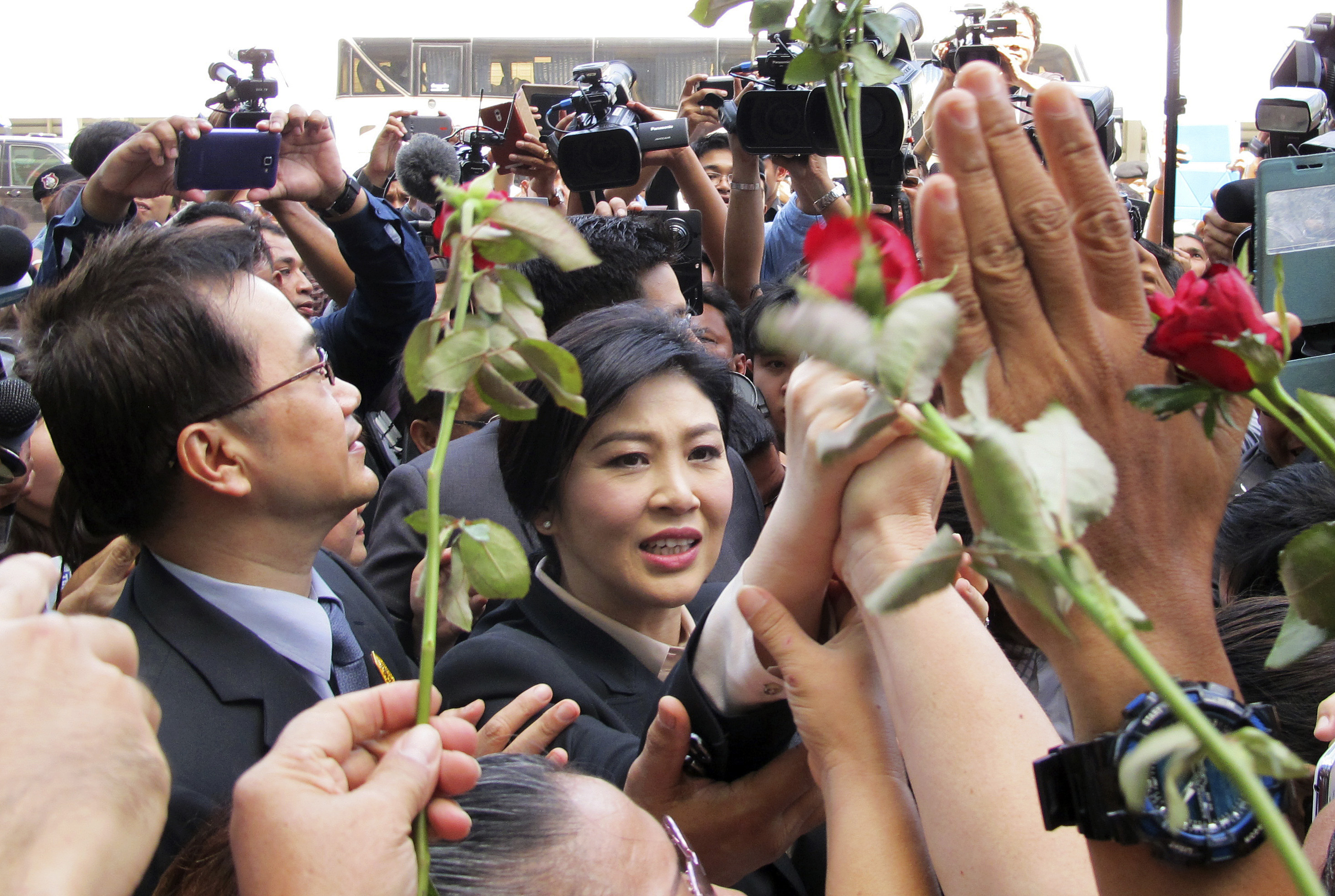 Thailand's former Prime Minister Yingluck Shinawatra, center, walks through supporters as she leaves the Supreme Court in Bangkok, Thailand, Tuesday, May 19, 2015.