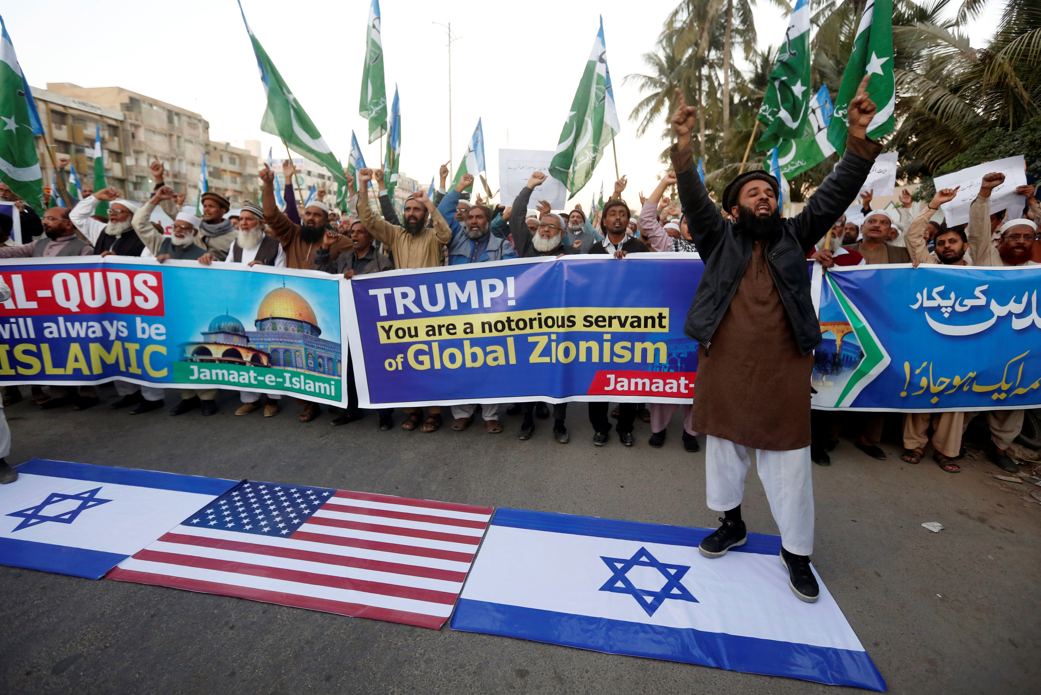 A supporter of religious and political party Jamaat-e-Islami chants slogans with others as he stands on Israeli flag during a protest against U.S. President Donald Trump's decision to recognize Jerusalem as the capital of Israel, in Karachi, Pakistan...