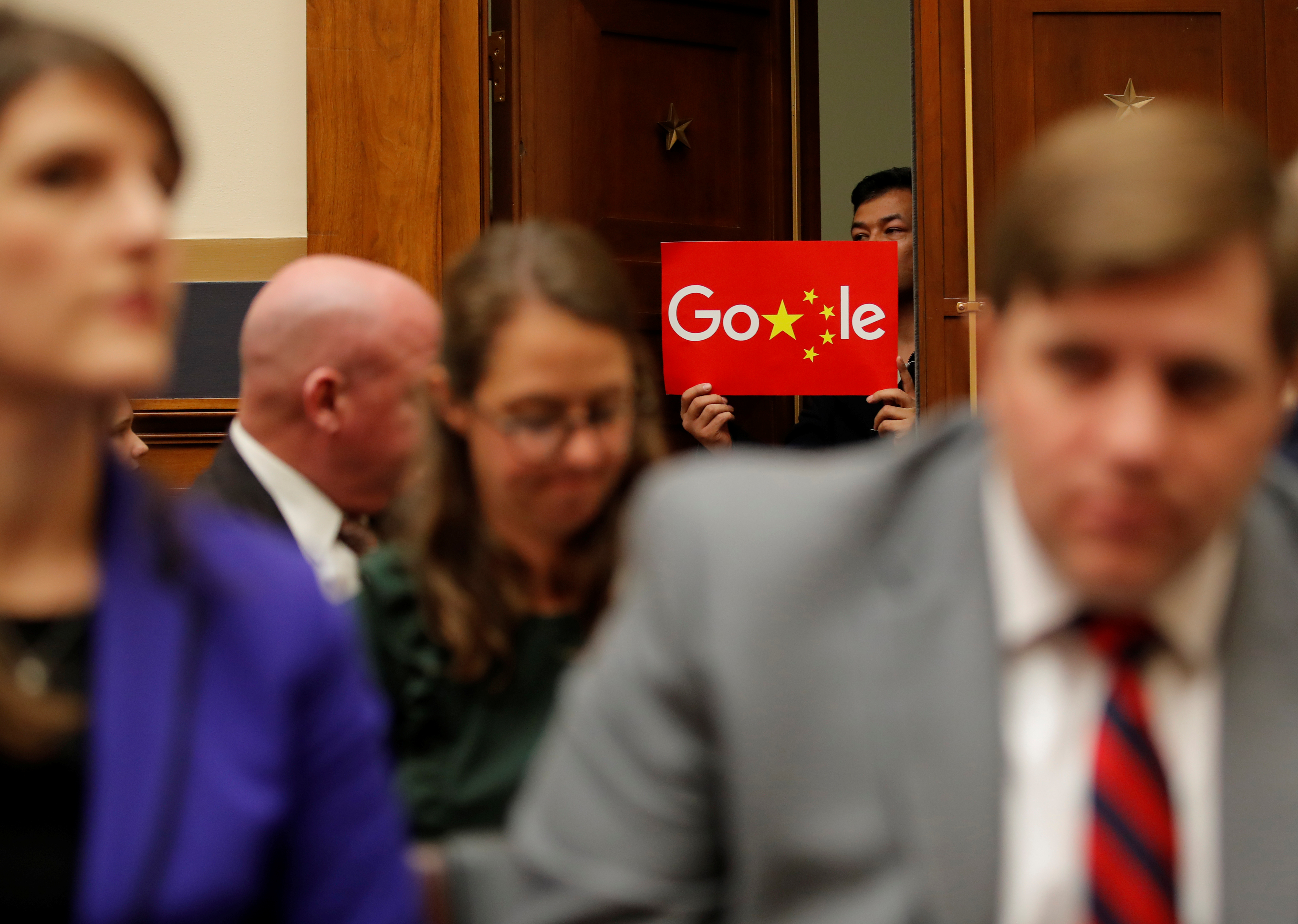 A demonstrator holds up a sign in the doorway as Google CEO Sundar Pichai testifies at a House Judiciary Committee on greater transparency in Washington, Dec. 11, 2018.