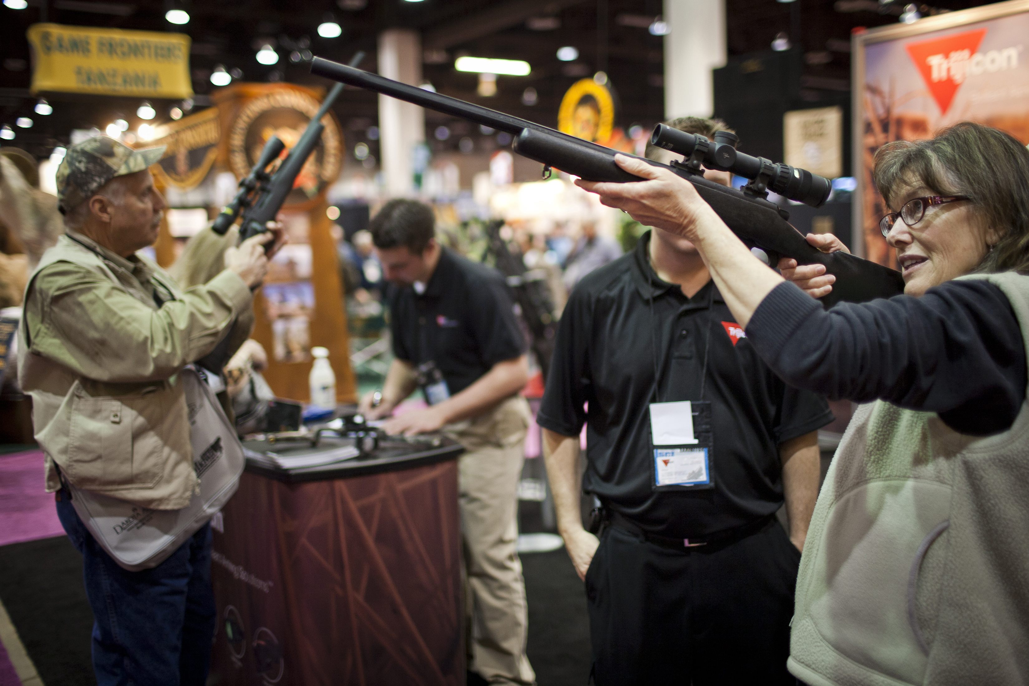 FILE - Kathy Hansen, right, tests a Trijicon rifle scope at the Safari Club International Convention in Reno, Nevada, Jan. 29, 2011.