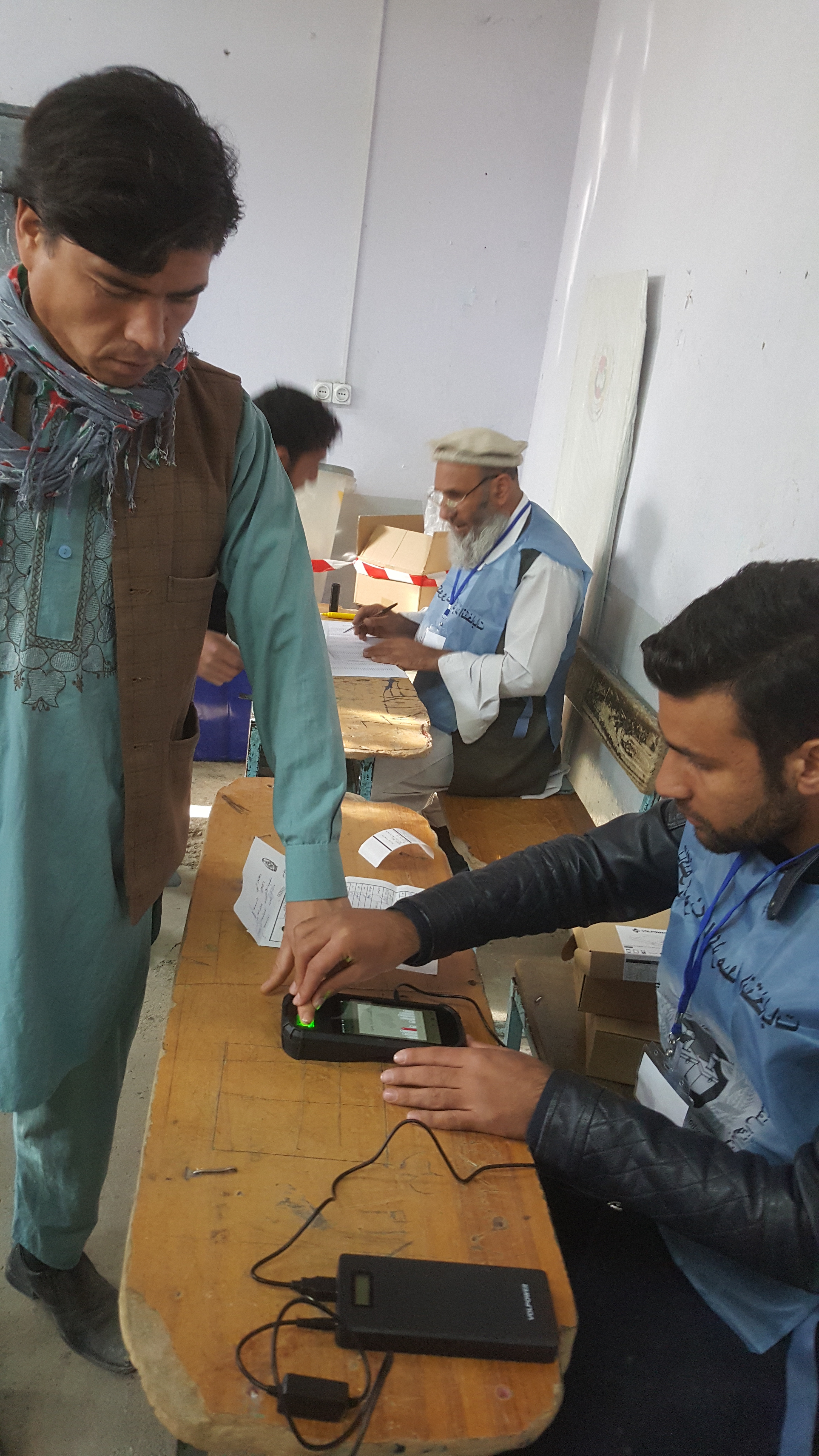 A man in a Kabul polling station is getting his fingerprints taken on the new biometrics system introduced to reduce fraud in elections, Oct. 20, 2018.