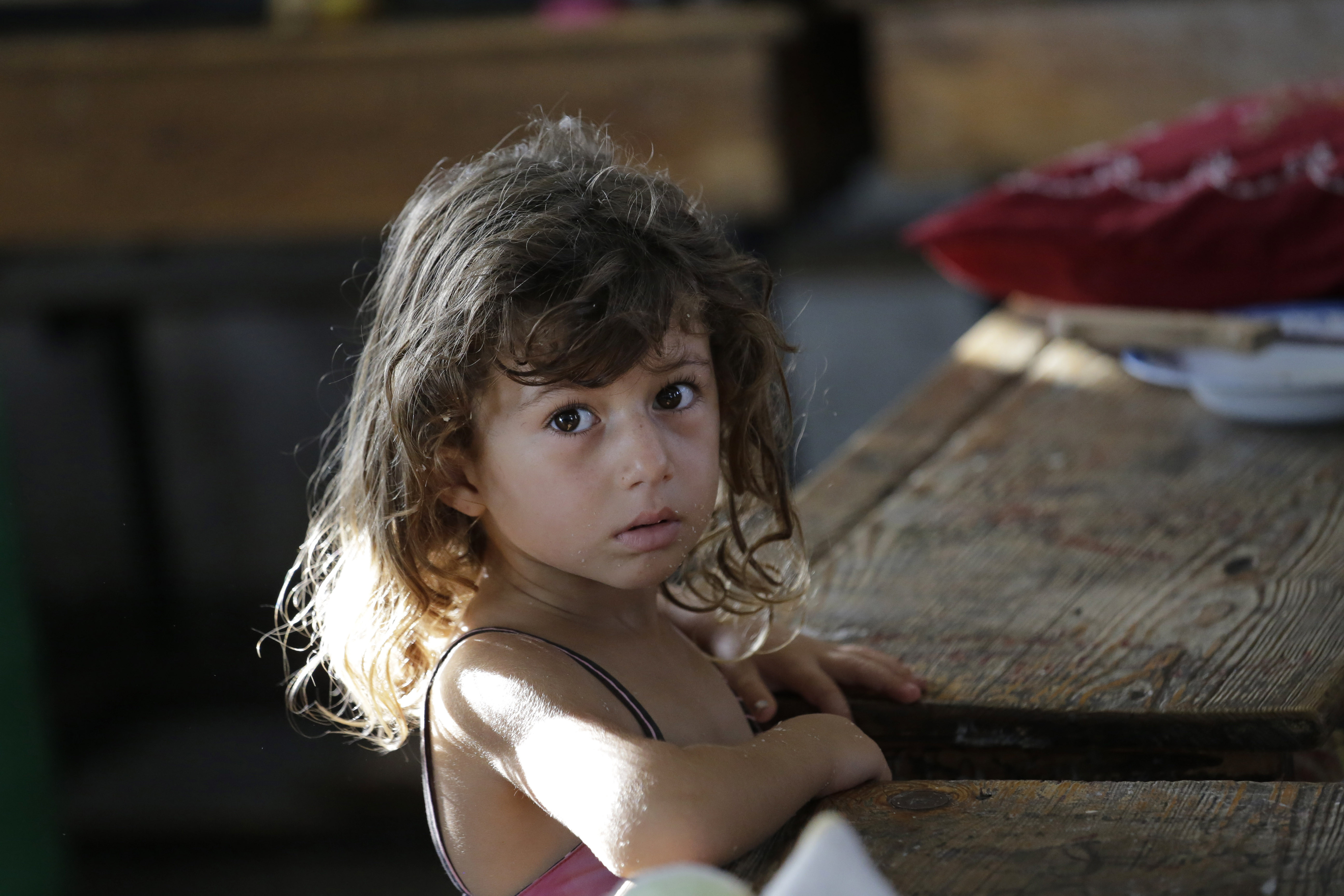 Hajar Muharram, 5, sits in a classroom where the family of seven now live, at a U.N. school, in Beit Lahiya, northern Gaza Strip,  Thursday, July 31, 2014.