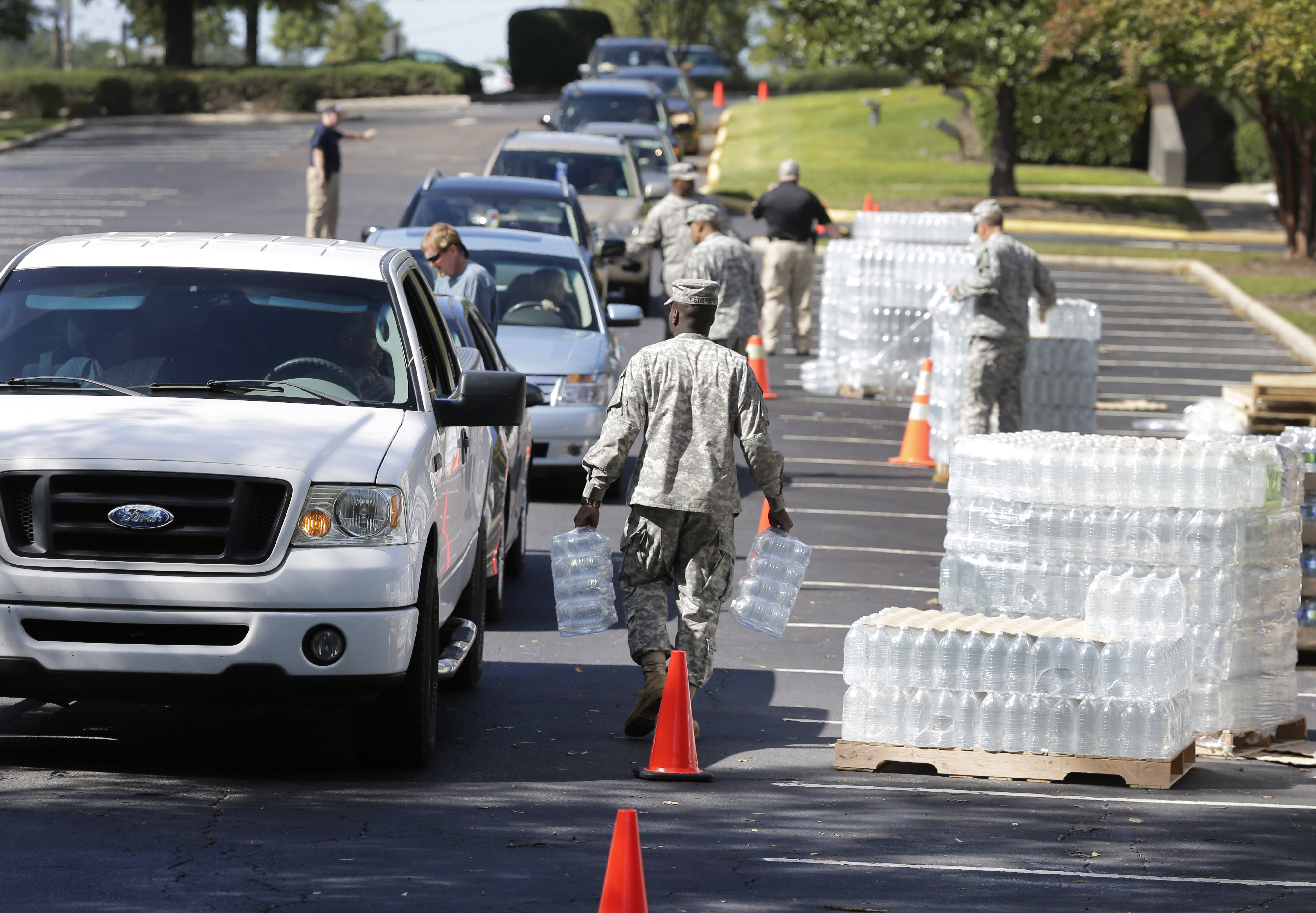 National Guard members hand out water to residents in Columbia, S.C., Oct. 6, 2015.  Water distribution remained a key problem Tuesday across much of the state.