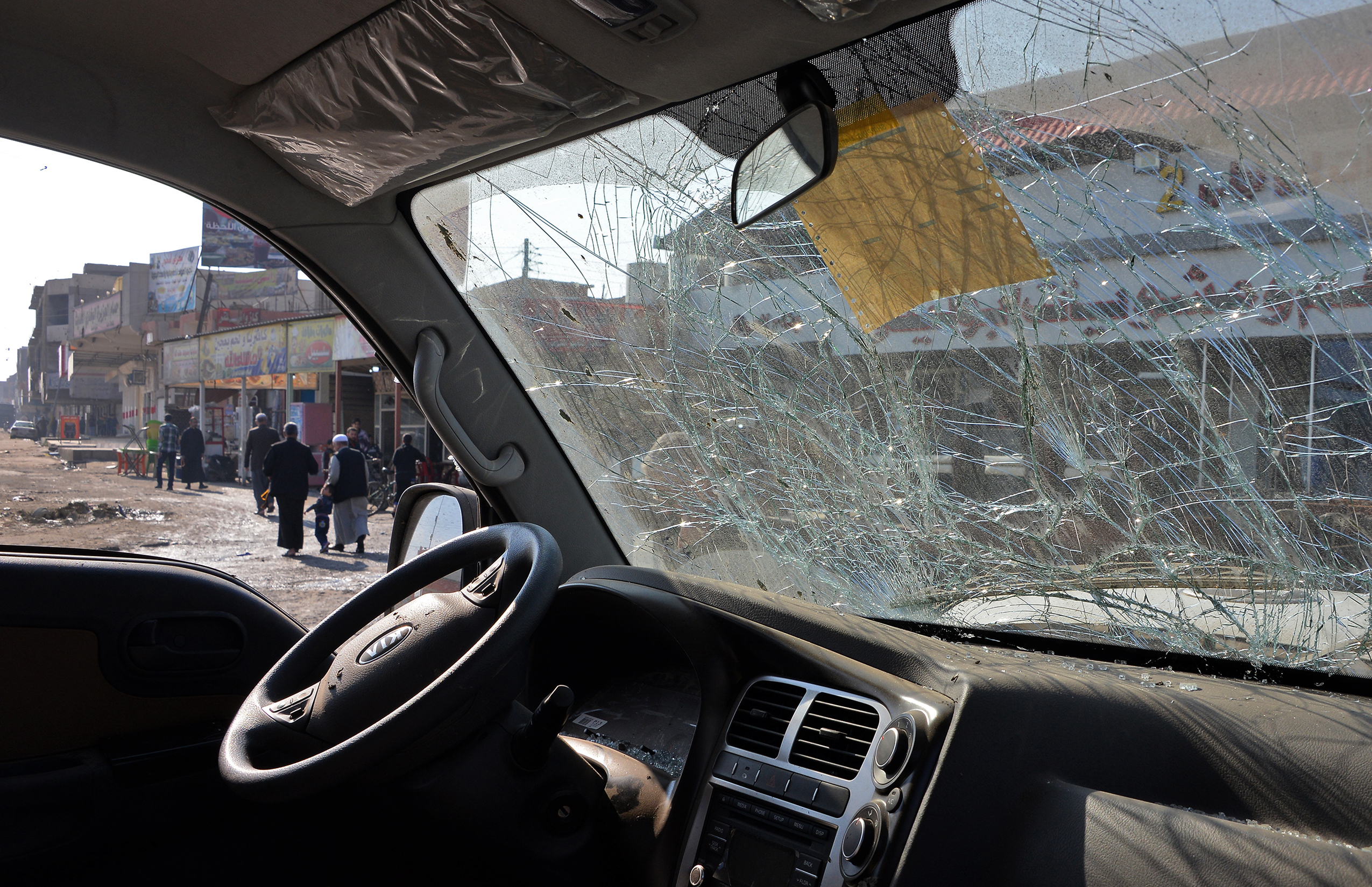 Iraqis are seen through a damaged car in Mosul, Iraq, Nov. 9, 2018. A car bomb that killed three people and wounded a dozen on Nov. 8, 2018, the first such attack since jihadists were ousted from the city last year.