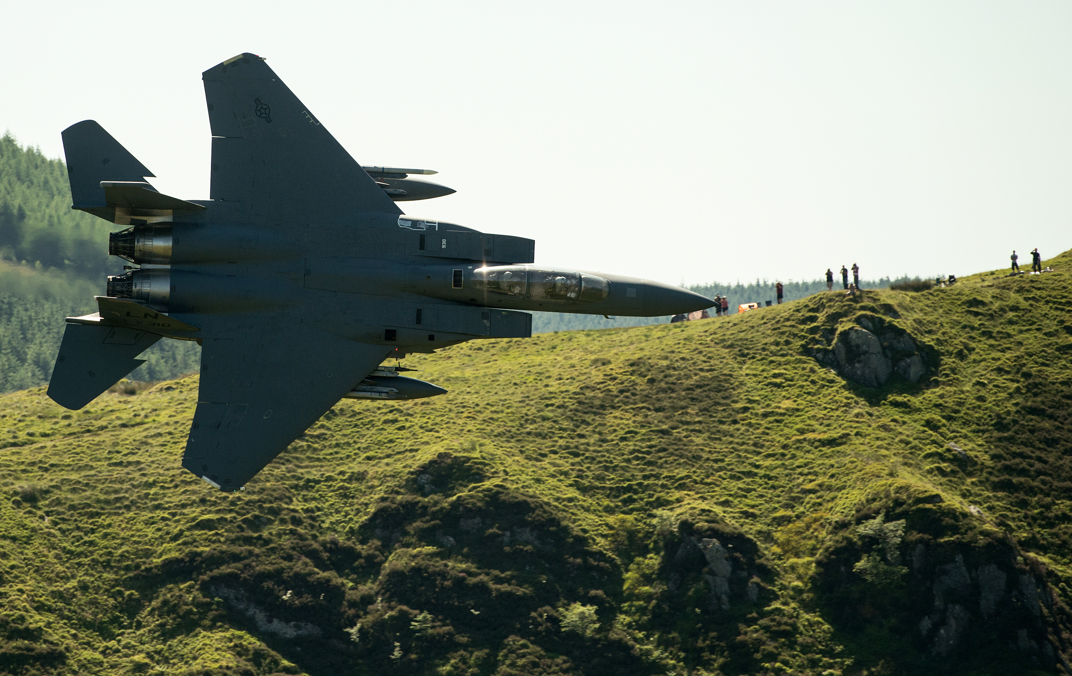 Military aircraft enthusiasts watch as a United States Air Force (USAF) F-15 fighter jet as it travels at low altitude through the 'Mach Loop' series of valleys near Dolgellau, north Wales on June 26, 2018.