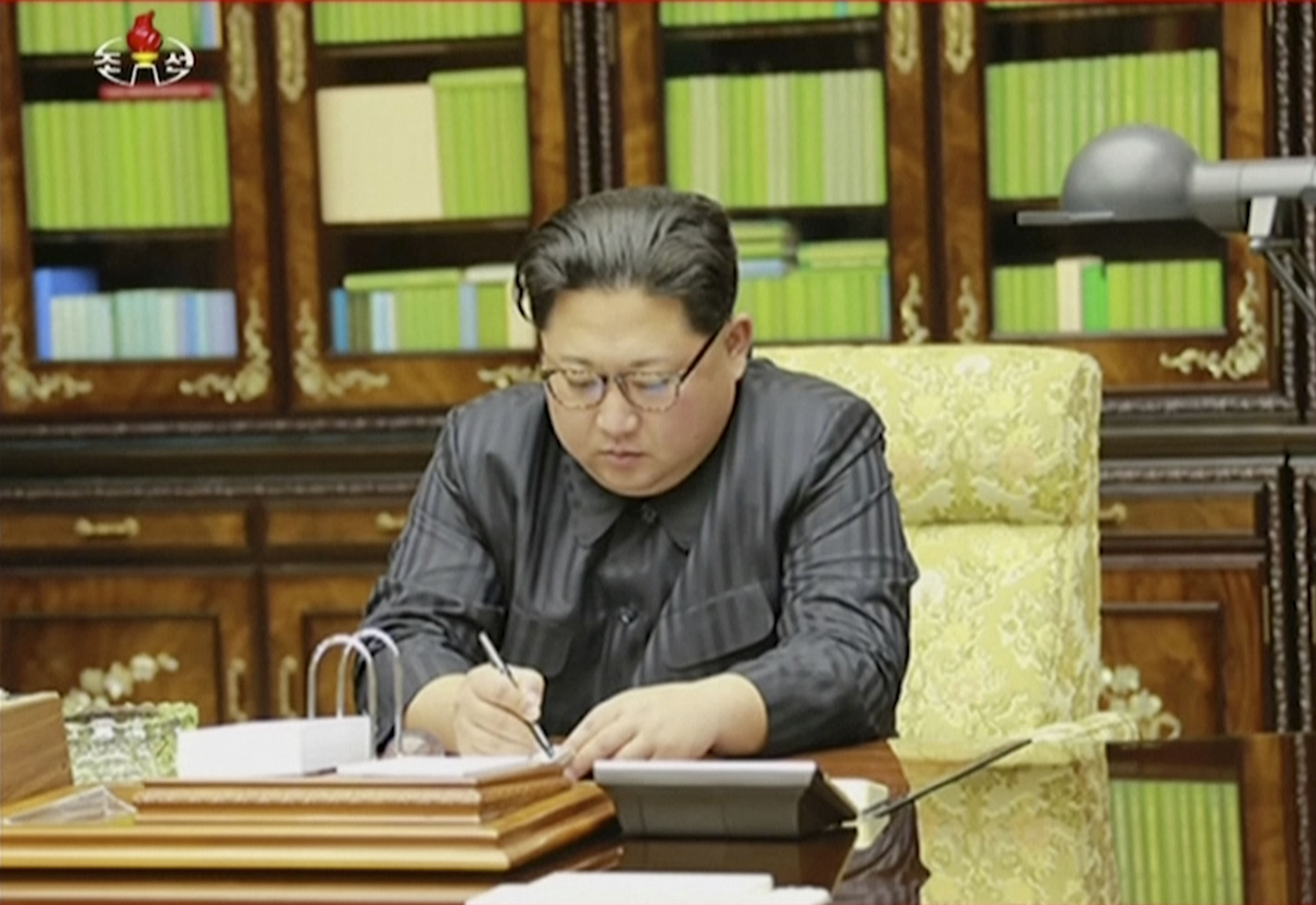 This image made from video of a news bulletin aired by North Korea's KRT on Nov. 29, 2017, shows an image of North Korea's leader Kim Jong Un signing what is said to be a document on Nov. 28, 2017, authorizing a missile test.