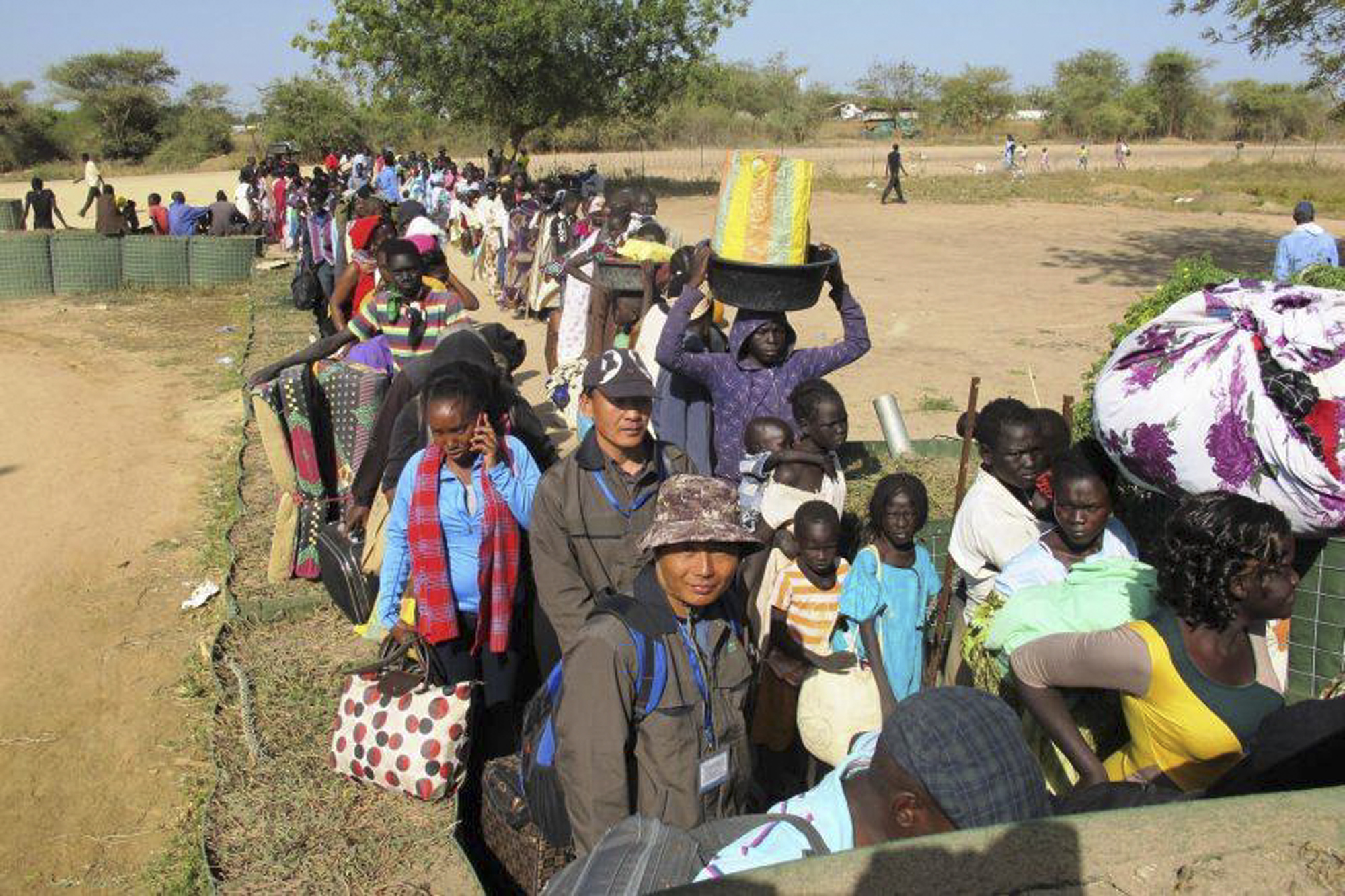 In this photo taken Wednesday, Dec. 18, 2013 and released by the United Nations Mission in South Sudan (UNMISS), civilians fleeing violence seek refuge at the UNMISS compound in Bor, capital of Jonglei state, in South Sudan.